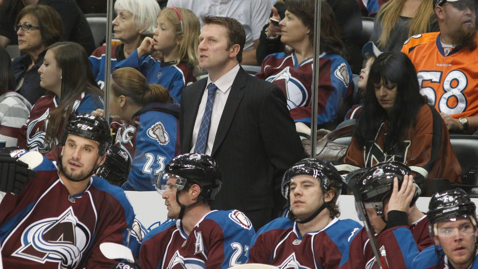 Colorado Avalanche head coach Joe Sacco, back, looks on as his players take a break during a time out against the Minnesota Wild in the second period of an NHL hockey game in Denver on Saturday, April 27, 2013. (AP Photo/David Zalubowski)