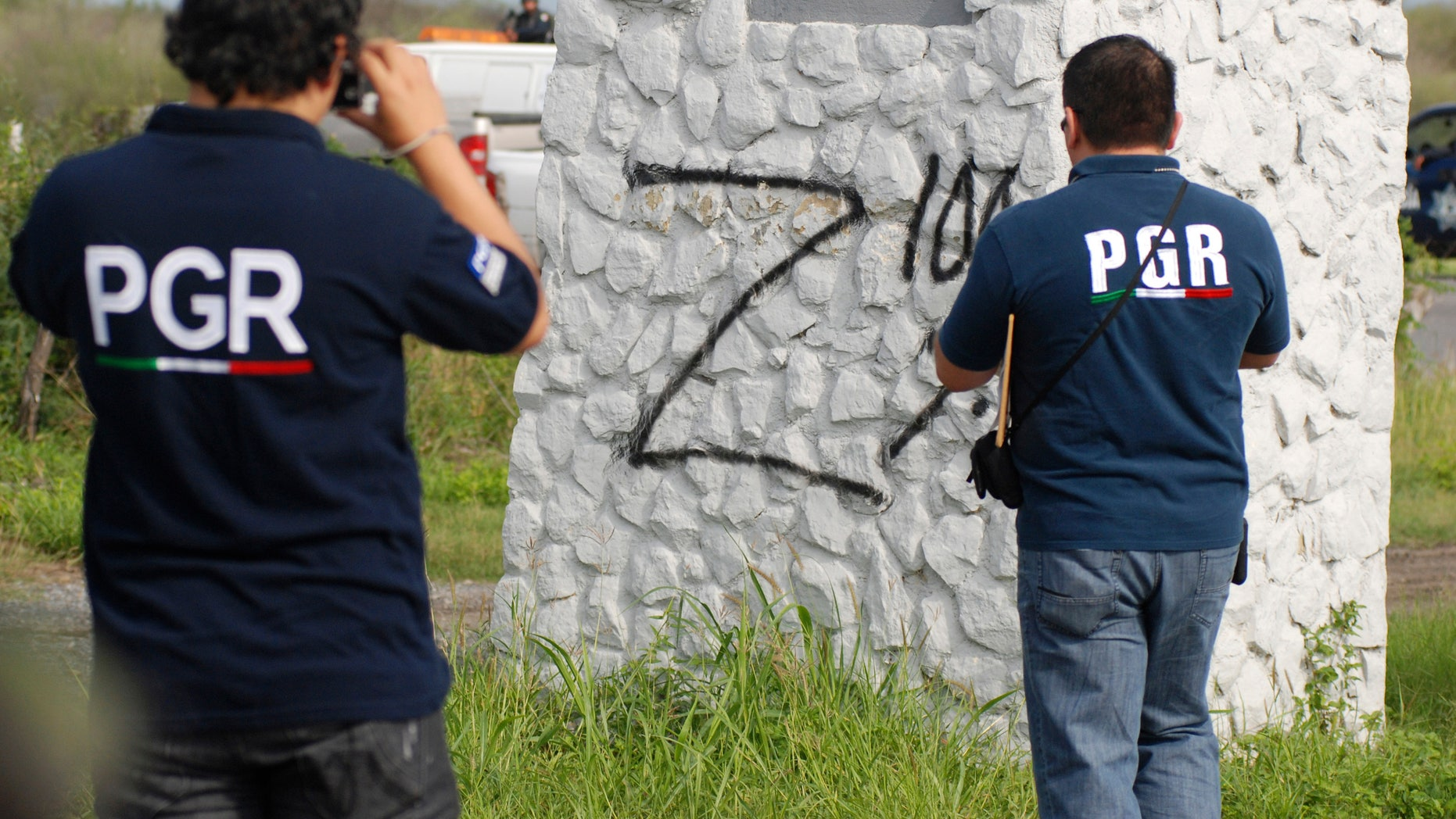 May 13: Federal agents take photographs of a sprayed 'Z,' the symbol of Zetas drug cartel, on a pillar at a crime scene in the municipality of Cadereyta.