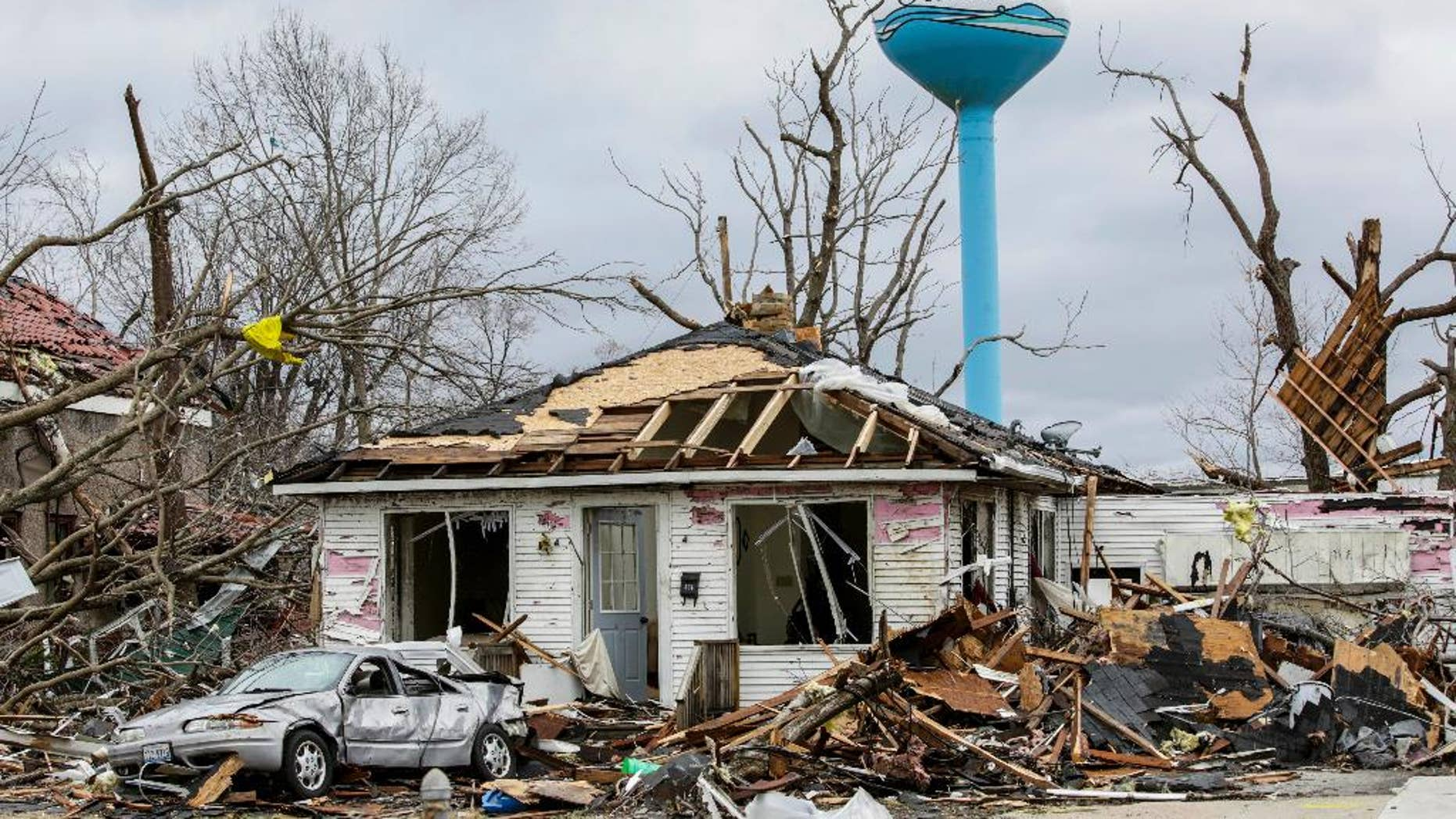 """Debbie Loughridge's damaged home and car are seen among debris in Naplate, Ill., Wednesday, March 1, 2017. Loughridge and her son rode out the storm in the bathtub. """"All I heard was the wind and the breaking glass. Like an explosion of glass,"""" she said. In the small community of Naplate, next to Ottawa, about a quarter of the roughly 200 homes were damaged, Fire Chief John Nevins said. (AP Photo/Teresa Crawford)"""