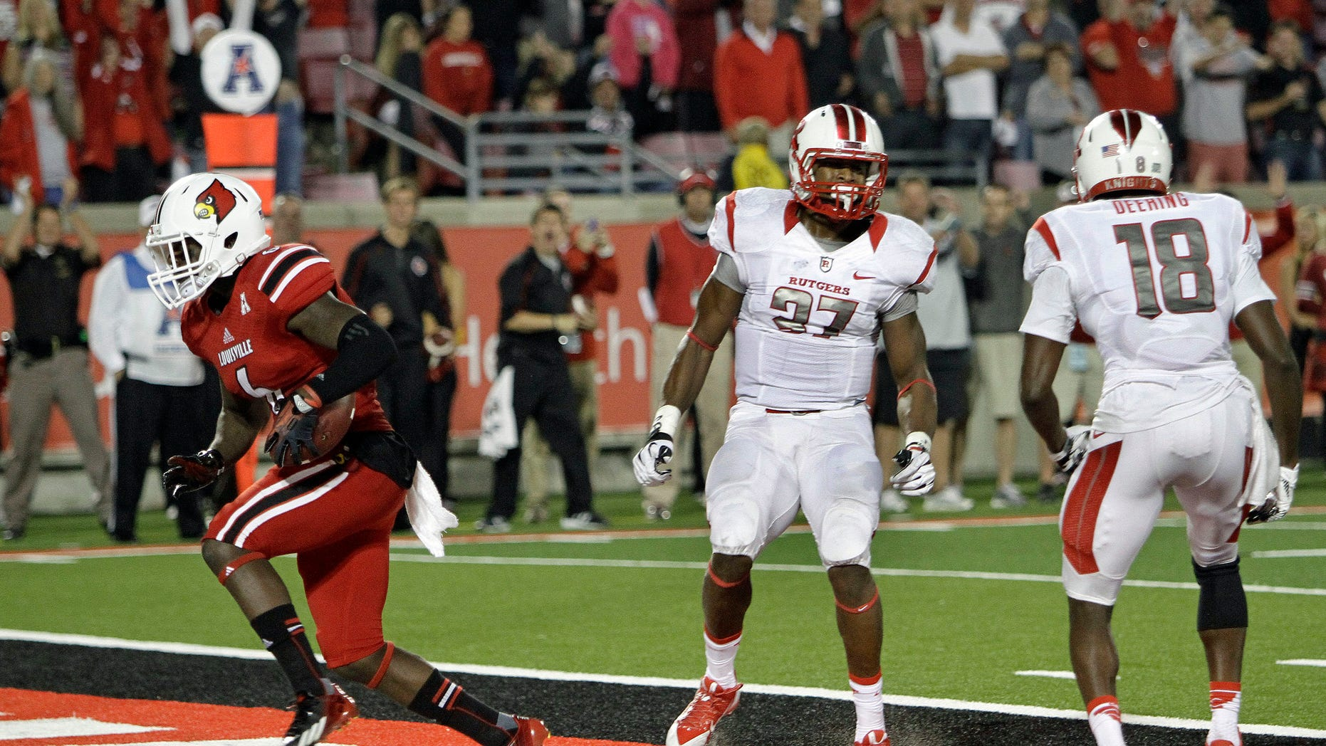 Louisville's Eli Rogers, left, splits Rutgers defenders Jamal Merrell (27) and Jeremy Deering (18) to score on a touchdown reception late in the fourth quarter in their NCAA college football game in Louisville, Ky., Thursday, Oct. 10, 2013. Louisville beat Rutgers 24-10.  (AP Photo/Garry Jones)