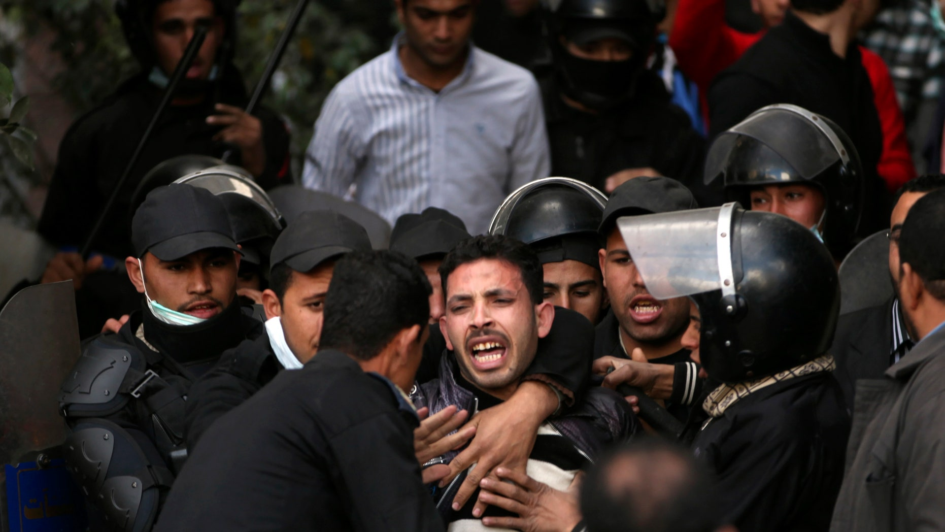 FILE - In this Wednesday, Jan. 30, 2013 file photo, Egyptian riot police arrest a man during clashes with protesters near Tahrir Square in Cairo, Egypt. With near impunity and the backing of the Islamist president, Egyptian police have over the past week used excessive and often deadly force against protesters across much of the country, regaining their Mubarak-era notoriety as a tool of repression. With nearly 60 people dead and hundreds injured, police have re-emerged as a significant political player after spending the past two years on the sidelines. (AP Photo/Khalil Hamra, File)