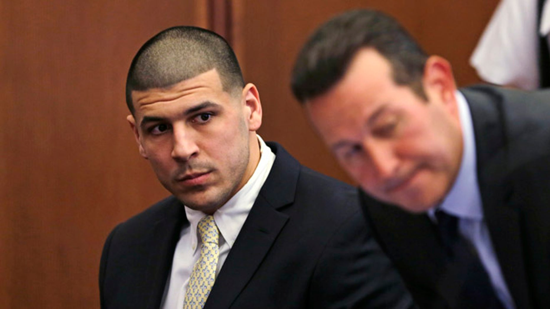 FILE - In this Thursday, July 21, 2016 file photo, Former New England Patriots wide receiver Aaron Hernandez, left, looks down the table at his legal team as his new defense attorney Jose Baez, right, takes a seat during a court appearance at Plymouth Superior Court in Plymouth, Mass. Hernandez is due in Suffolk Superior Court on Tuesday, Aug. 16, for a hearing in the 2012 killings of two men outside a Boston nightclub. Hernandez has pleaded not guilty. (AP Photo/Charles Krupa, Pool, File)