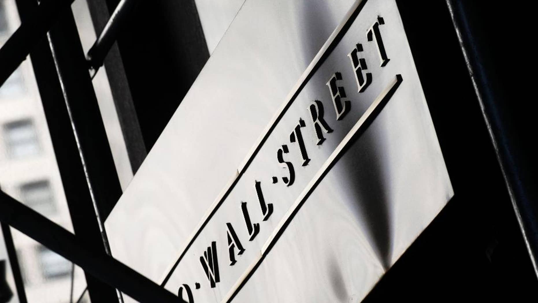 FILE - This July 15, 2013, file photo, shows a sign for Wall Street outside the New York Stock Exchange, in New York. Global stocks were mostly lower Tuesday, Sept. 23, 2014, following Wall Street's tumble but China rebounded after unexpectedly strong manufacturing eased fears of an economic slowdown. (AP Photo/Mark Lennihan, File)