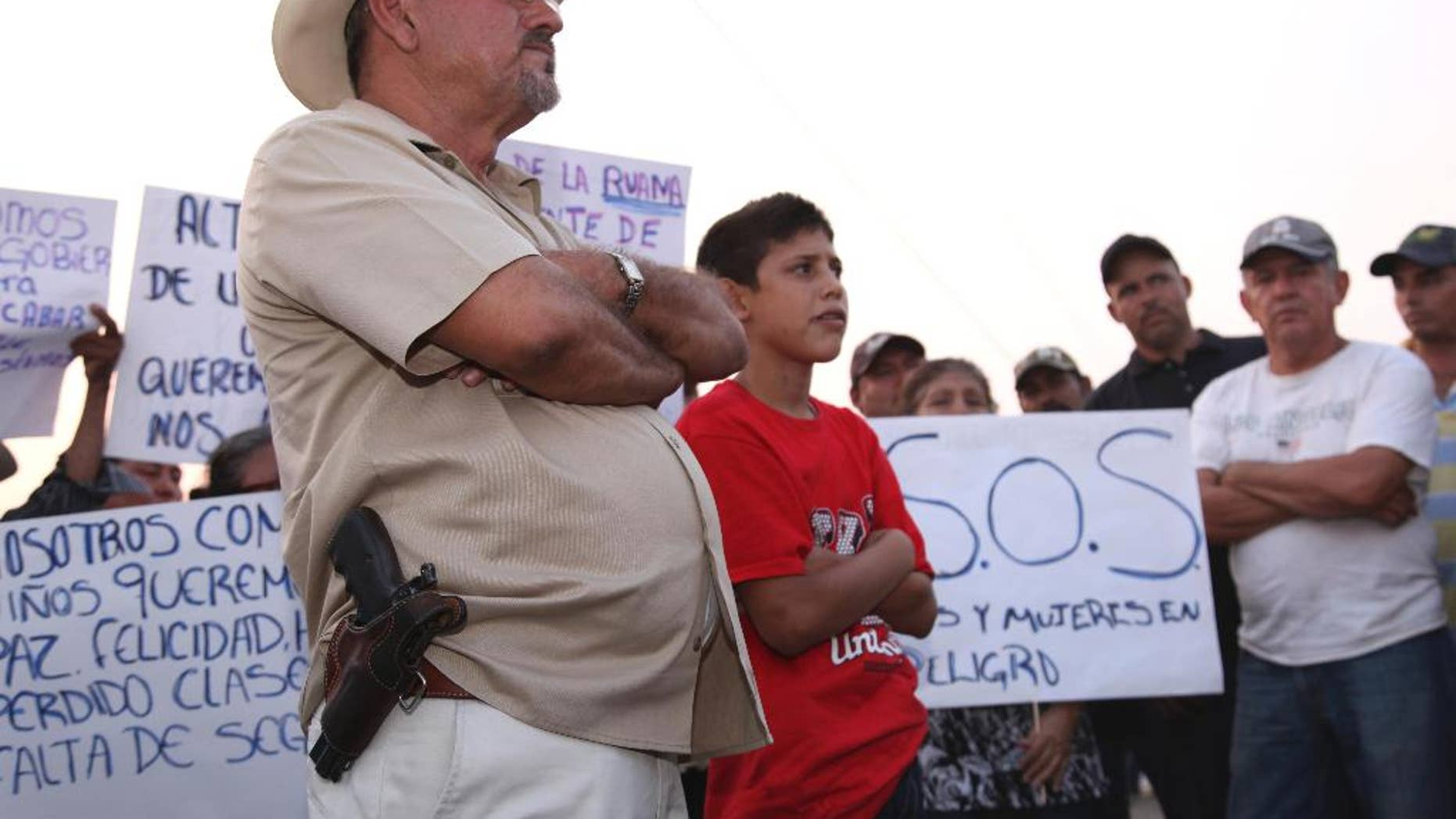 """FILE - In this May 19, 2013 file photo, Hipolito Mora, leader of a local self-defense movement, stands with a side-arm as residents protest extortion fees and kidnappings by the Knights of Templar drug cartel in La Ruana, Mexico. On Dec. 16, 2014, Mora's group had a deadly shootout with a rival rural police force led by Luis Antonio Torres, better known as """"Simon the American,"""" that left 11 people dead, including Mora's son, in the remote mountain town of La Ruana, Michoacan. On Saturday, Jan. 3, 2015, a judge said there was sufficient evidence against Mora and his followers of involvement in 10 homicides during the shootout to merit the launch of homicide proceedings. (AP Photo/Marco Ugarte, File)"""
