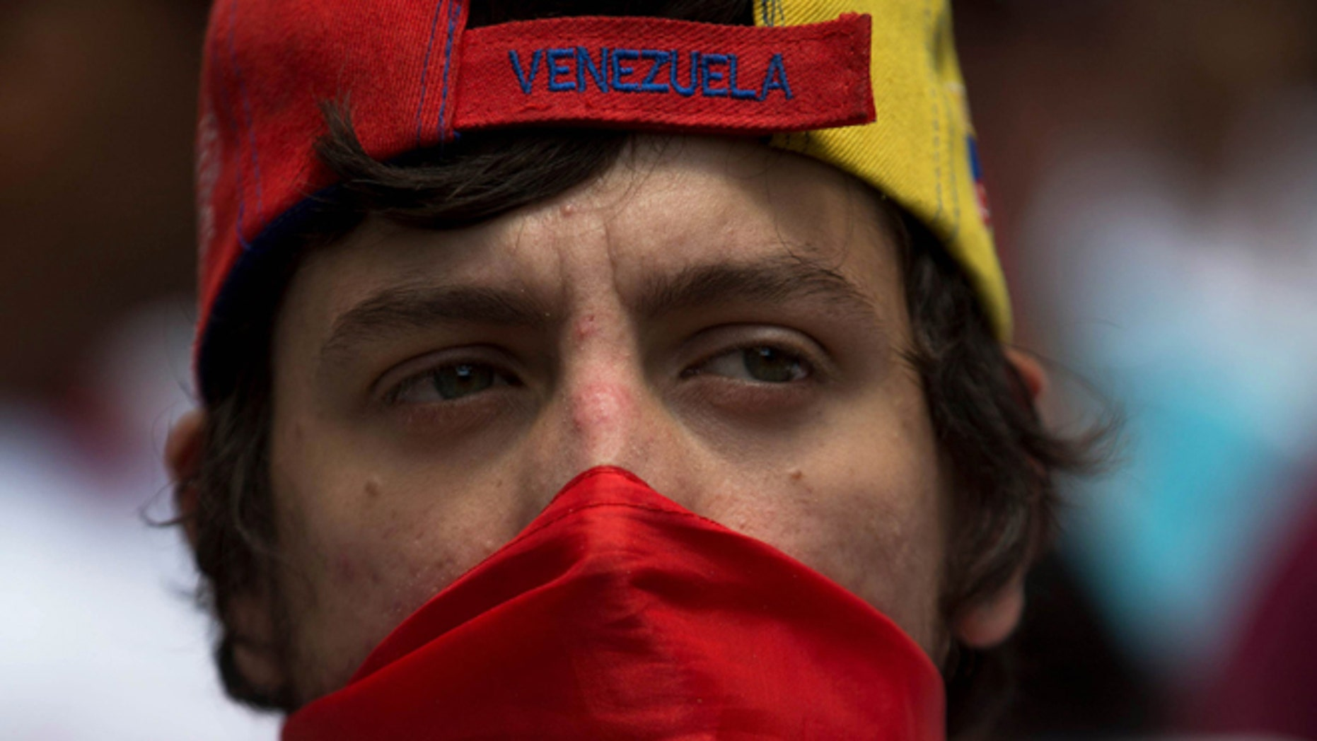 An opposition member covers his face with a Venezuelan flag during a protest in Caracas, Venezuela, Saturday, Feb. 28, 2015. Marchers are taking to the streets of Caracas in dueling protests, with one group calling attention to a crackdown on opponents of the government and another showing support for the embattled socialist administration.(AP Photo/Fernando Llano)