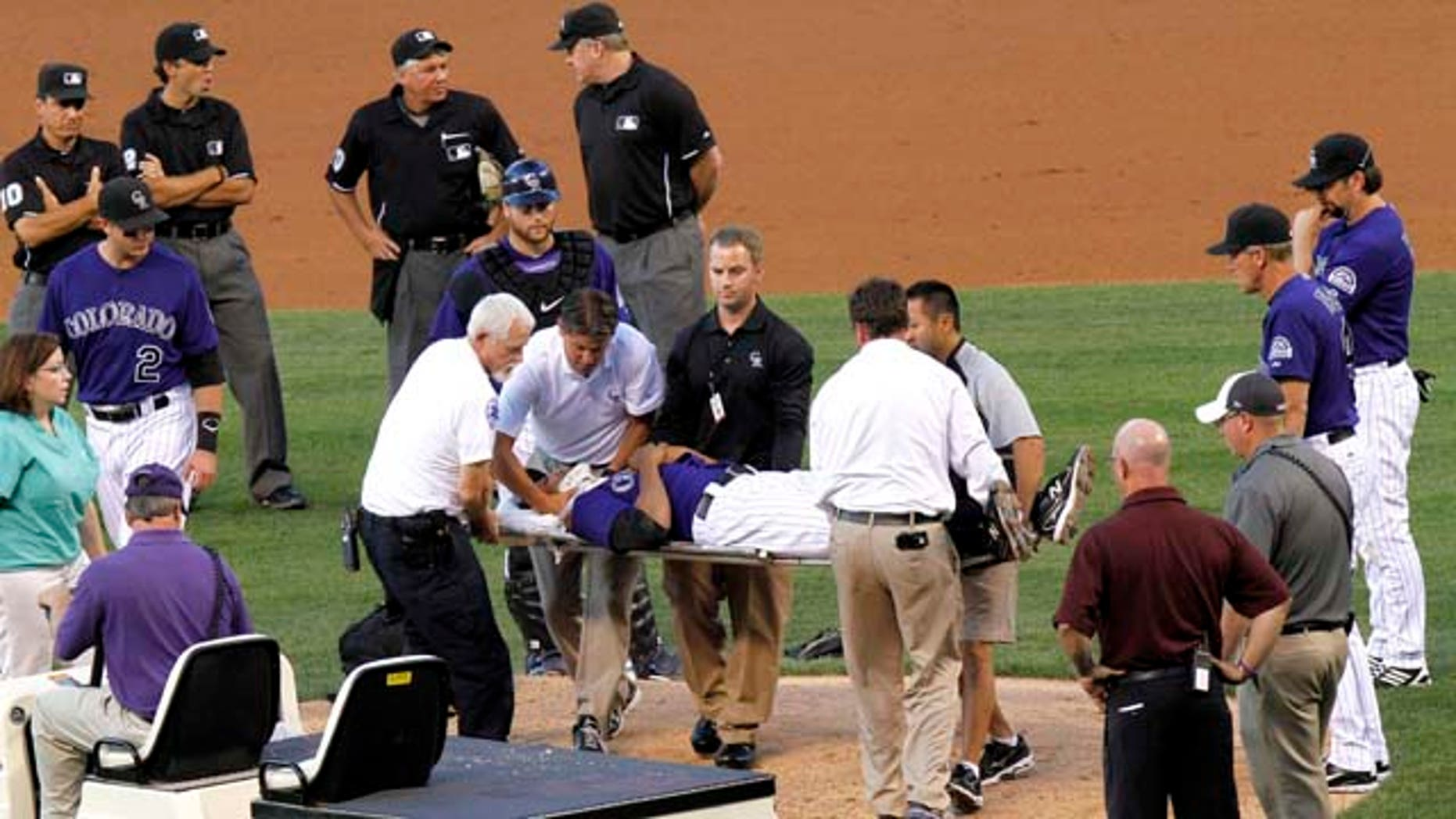 Colorado Rockies starting pitcher Juan Nicasio is surrounded by teammates and medical personnel on his way off the field after Washington Nationals' Ian Desmond hit him in the head with a line drive during the second inning of a baseball game Friday, Aug. 5, 2011 in Denver. (AP Photo/Barry Gutierrez)