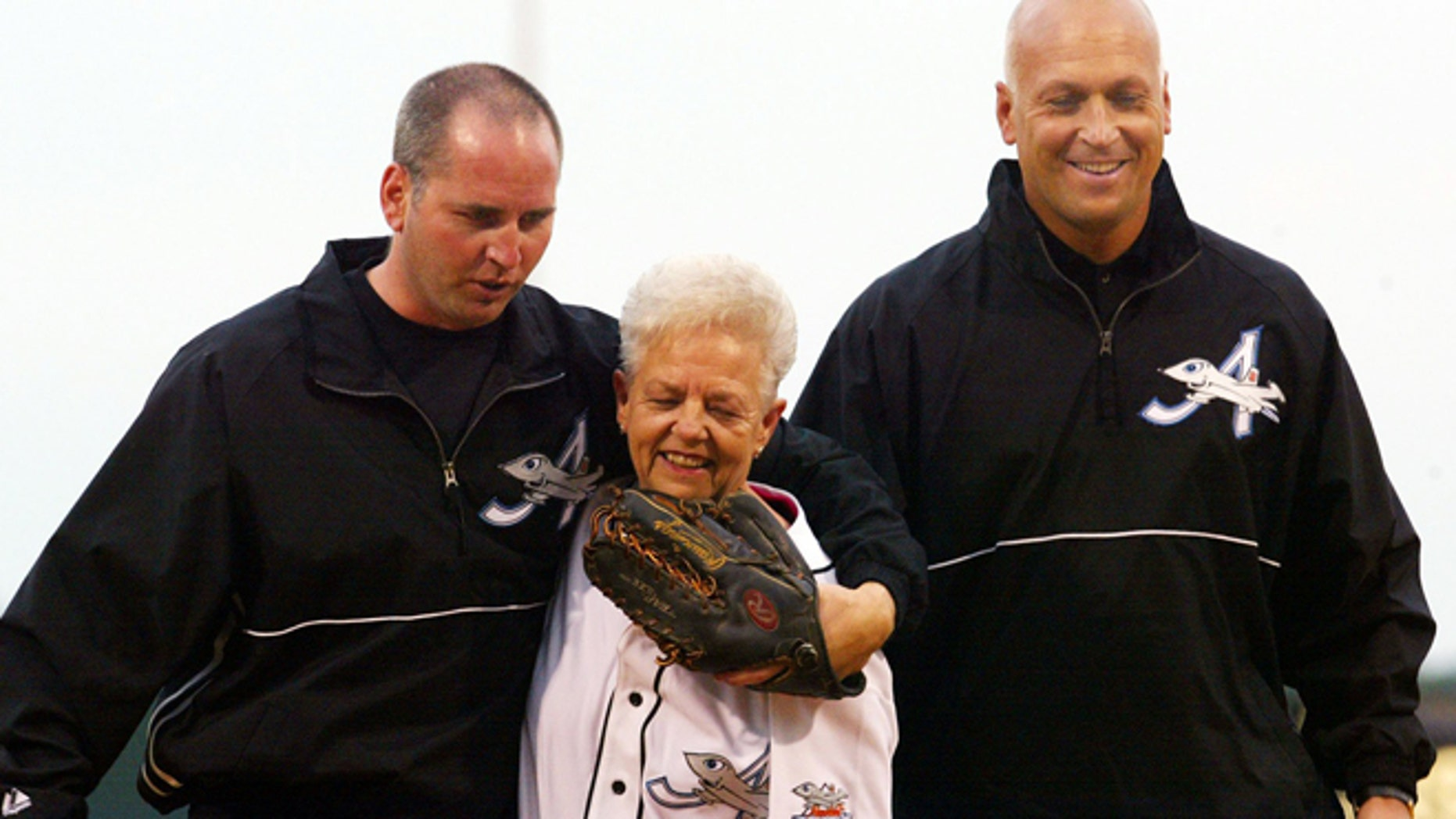 June 2002: Cal Ripken Jr., right, owner of the Aberdeen IronBirds, and his brother, Bill, walking off the field with their  mother after she threw out the first pitch.