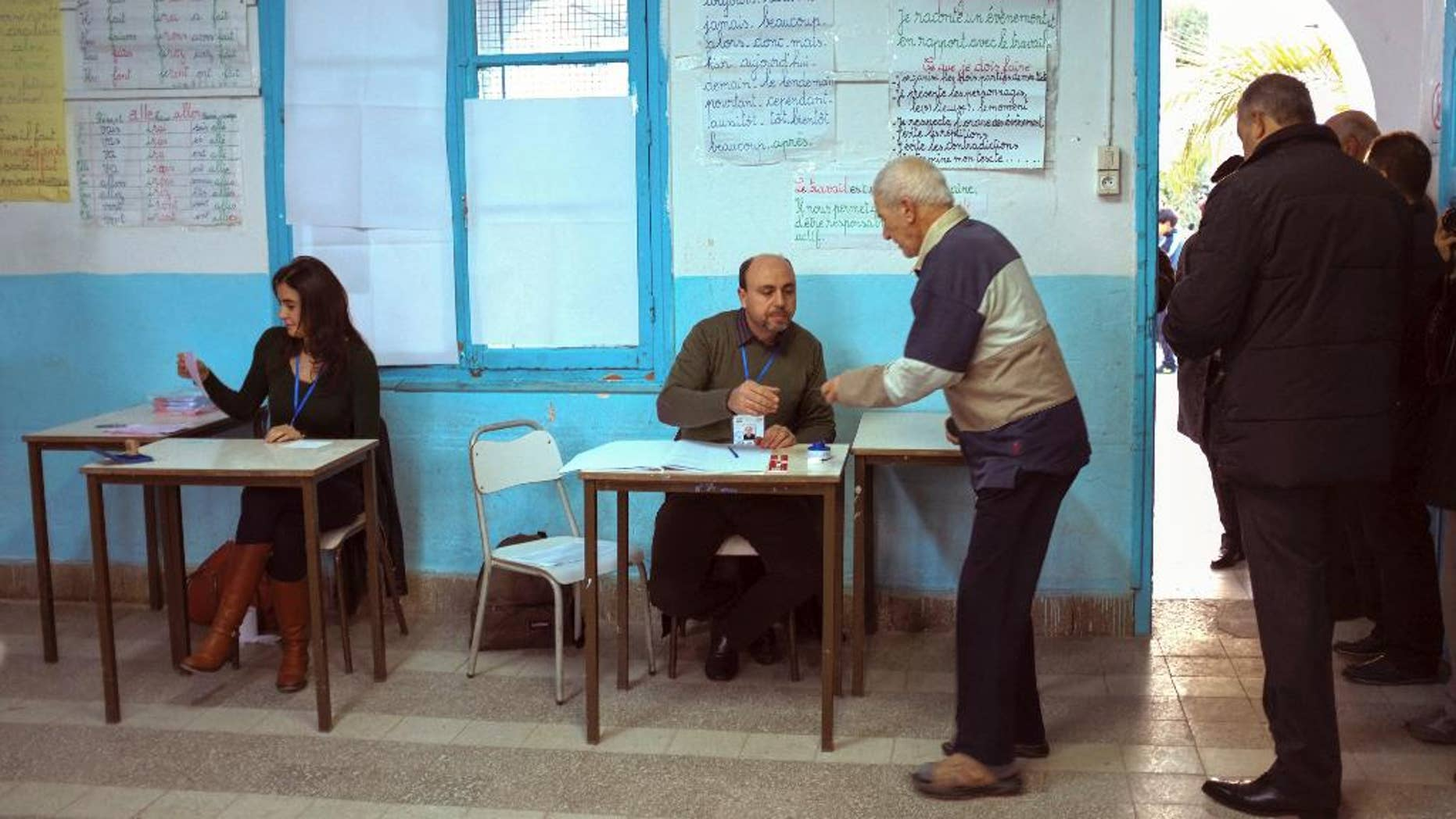 Tunisians check voters' ID prior to cast their ballots in a polling station in Tunis, Tunisia, Sunday, Dec. 21, 2014.  Tunisians voted on Sunday for a new president in a runoff between a symbol of the country's previous regimes and a veteran human rights activist that came to power after the revolution of 2011.(AP Photo/Ilyess Osmane)