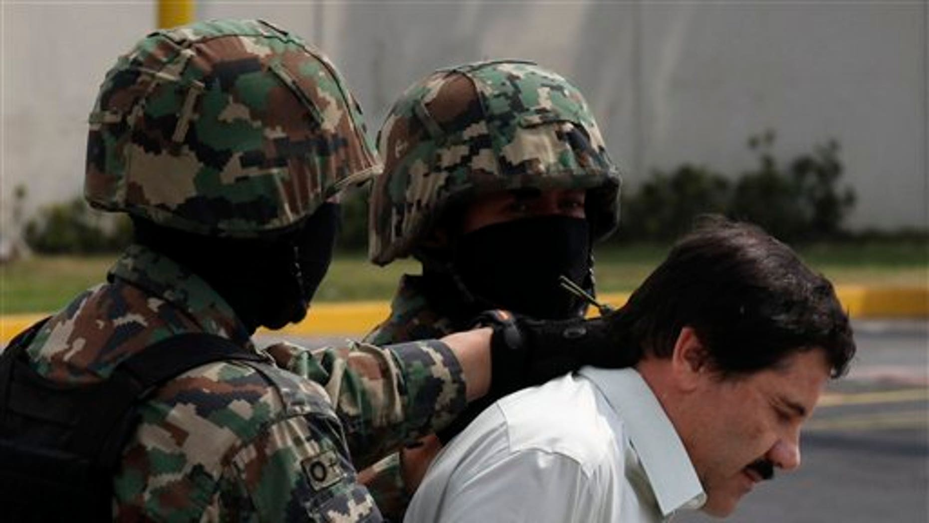 """Feb. 22, 2014: Joaquin """"El Chapo"""" Guzman, in handcuffs, is escorted to a helicopter by Mexican navy marines in Mexico City, Mexico."""