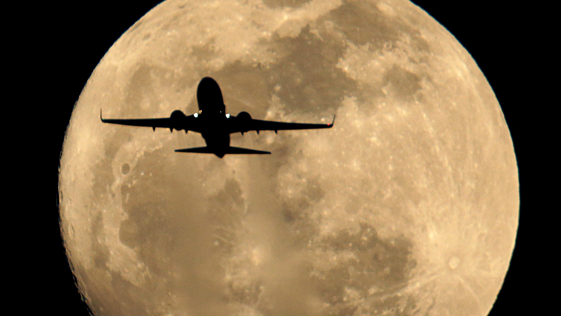 A Southwest Airlines jet is silhouetted against the rising full moon as it takes of from Sky Harbor Airport Sunday, Feb. 24, 2013 in Phoenix. (AP Photo/Charlie Riedel)