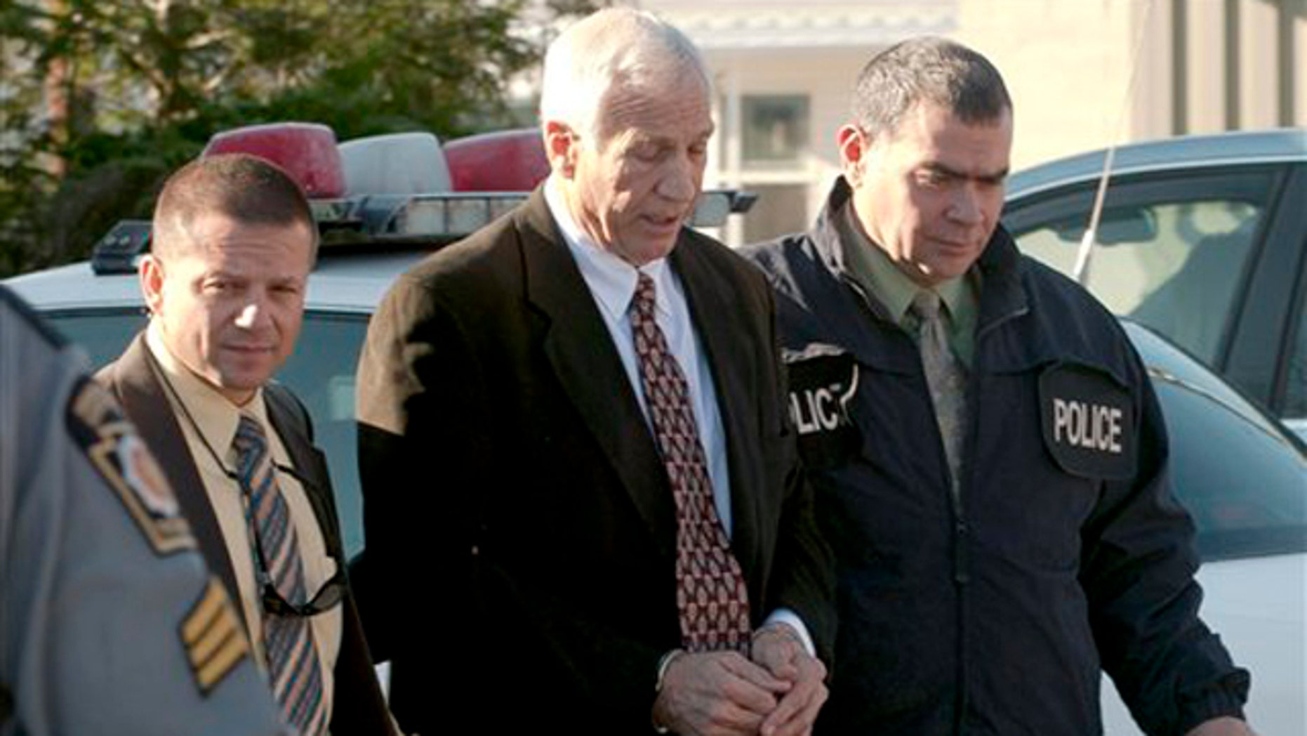 """Nov. 5: In this photo provided by the Pennsylvania Office of Attorney General, former Penn State football defensive coordinator Gerald """"Jerry"""" Sandusky, is escorted in handcuffs to a waiting police car in Bellefonte, Pa."""
