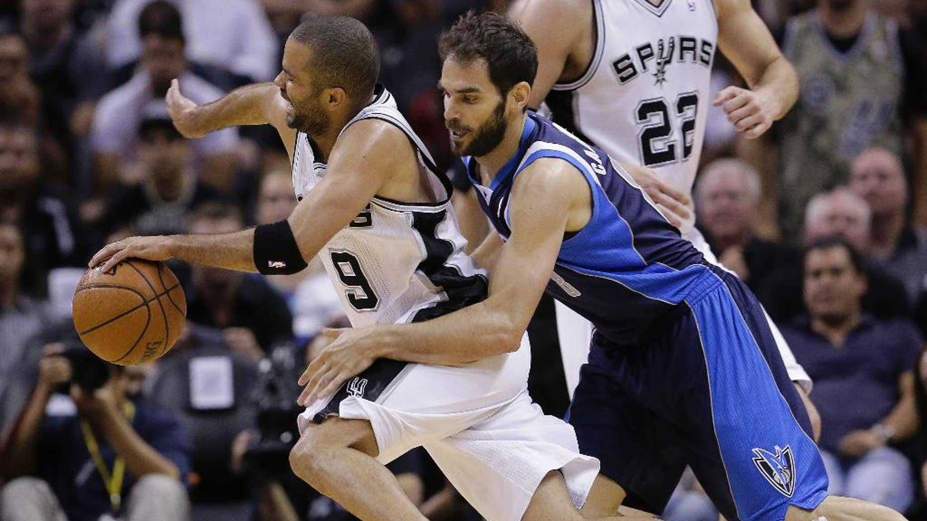 San Antonio Spurs' Tony Parker (9), of France, is fouled by Dallas Mavericks' Jose Calderon (8), of Spain, during the second half of Game 5 of the opening-round NBA basketball playoff series on Wednesday, April 30, 2014, in San Antonio. San Antonio won 109-103. (AP Photo/Eric Gay)