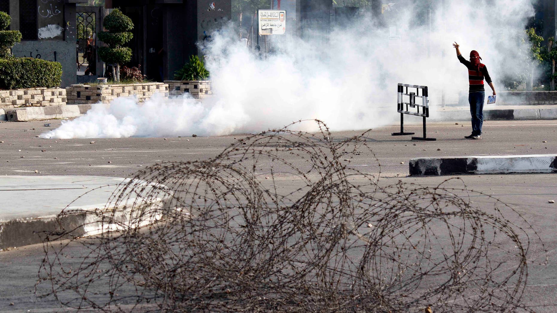 A masked protester stands in a cloud of tear gas during clashes with security forces dispersing several hundred pro- ousted President Mohammed Morsi university students who were rallying near Rabaah el-Adawiya, in eastern Cairo, Egypt, Monday, Oct. 28, 2013. As the protest got underway, army troops and police backed by armored vehicles blocked off the road leading to the site, creating a tense stand-off that lasted hours. By late afternoon, the students retreated to their campus, while pelting security forces with rocks.(AP Photo/Said Hamdy)