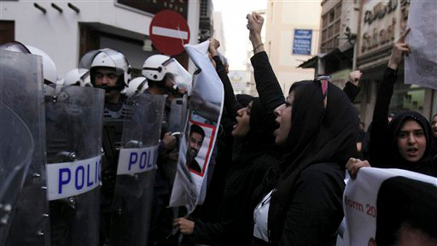 April 18, 2012: Bahraini anti-government activist Zainab al-Khawaja, second right, gestures and chants slogans in front of riot police during a protest in downtown Manama, Bahrain.