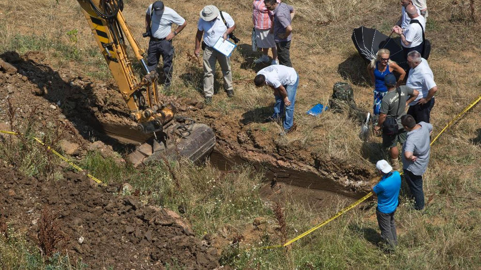 Yellow tape marks the site as an excavator digs a location that is being investigated at Pristina University campus following suspicions of a mass grave of people missing since the 1999 war, in Pristina on Wednesday, July 13, 2016. About 1,650 people remain missing since the end of the war with Serbia in 1999. (AP Photo/Visar Kryeziu)