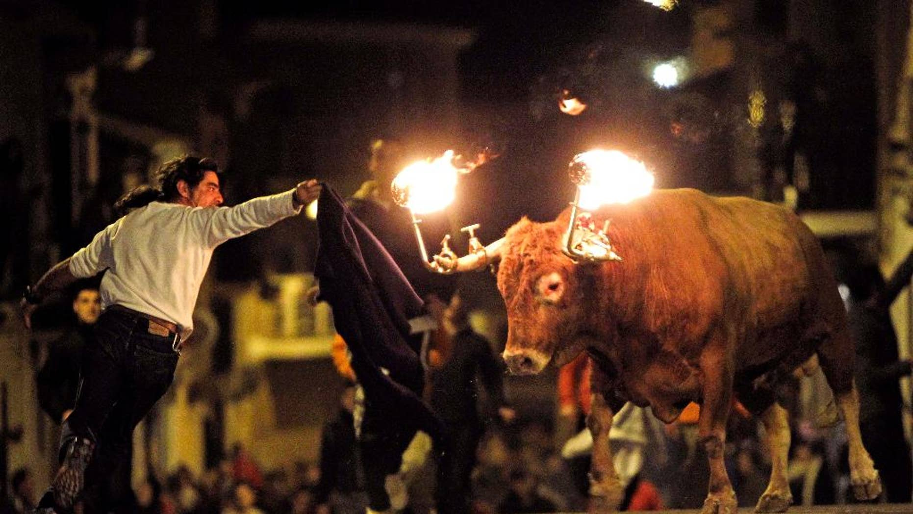 FILE - In this Jan. 17, 2010 file photo, a reveler runs away from a bull with flaming horns during a festivity in honor of Saint Anthony, the patron saint of animals, in the streets of Gilet, a town near Valencia, Spain. The city of Valencia has banned a longtime tradition where bulls are set loose on neighborhood streets with flaming balls of wax or fireworks affixed to their horns. Mayor Joan Ribo cited cruelty to animals for the ban approved Friday, June 10, 2016. The city council also cut funding for bull runs and bullfighting schools but did not move to ban bullfighting. (AP Photo/Alberto Saiz, File)