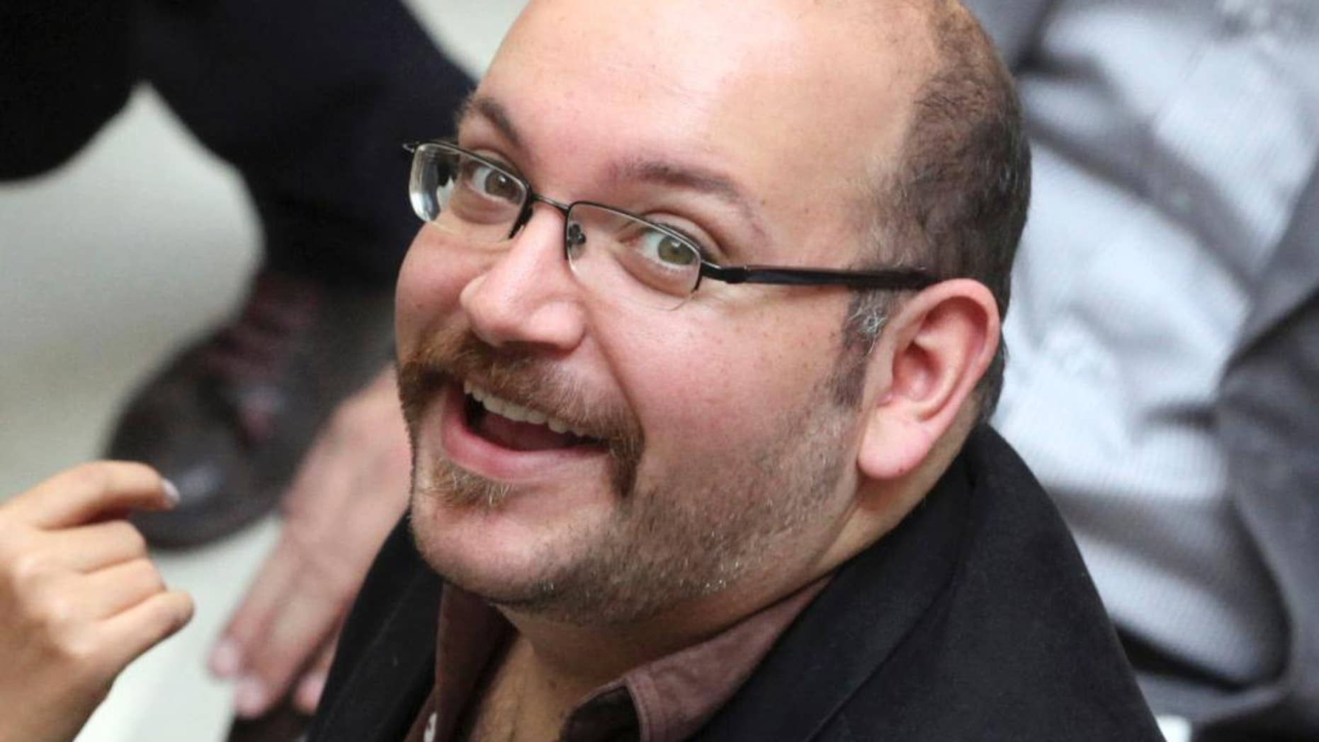 FILE - In this photo April 11, 2013 file photo, Jason Rezaian, an Iranian-American correspondent for the Washington Post, smiles as he attends a presidential campaign of President Hassan Rouhani in Tehran, Iran. Iran's official IRNA news agency reported that the verdict against Rezaian has been issued. Rezaian, the Post's Tehran bureau chief, is accused of charges including espionage in a closed-door trial that has been widely criticized by the U.S. government and press freedom organizations. (AP Photo/Vahid Salemi, File)