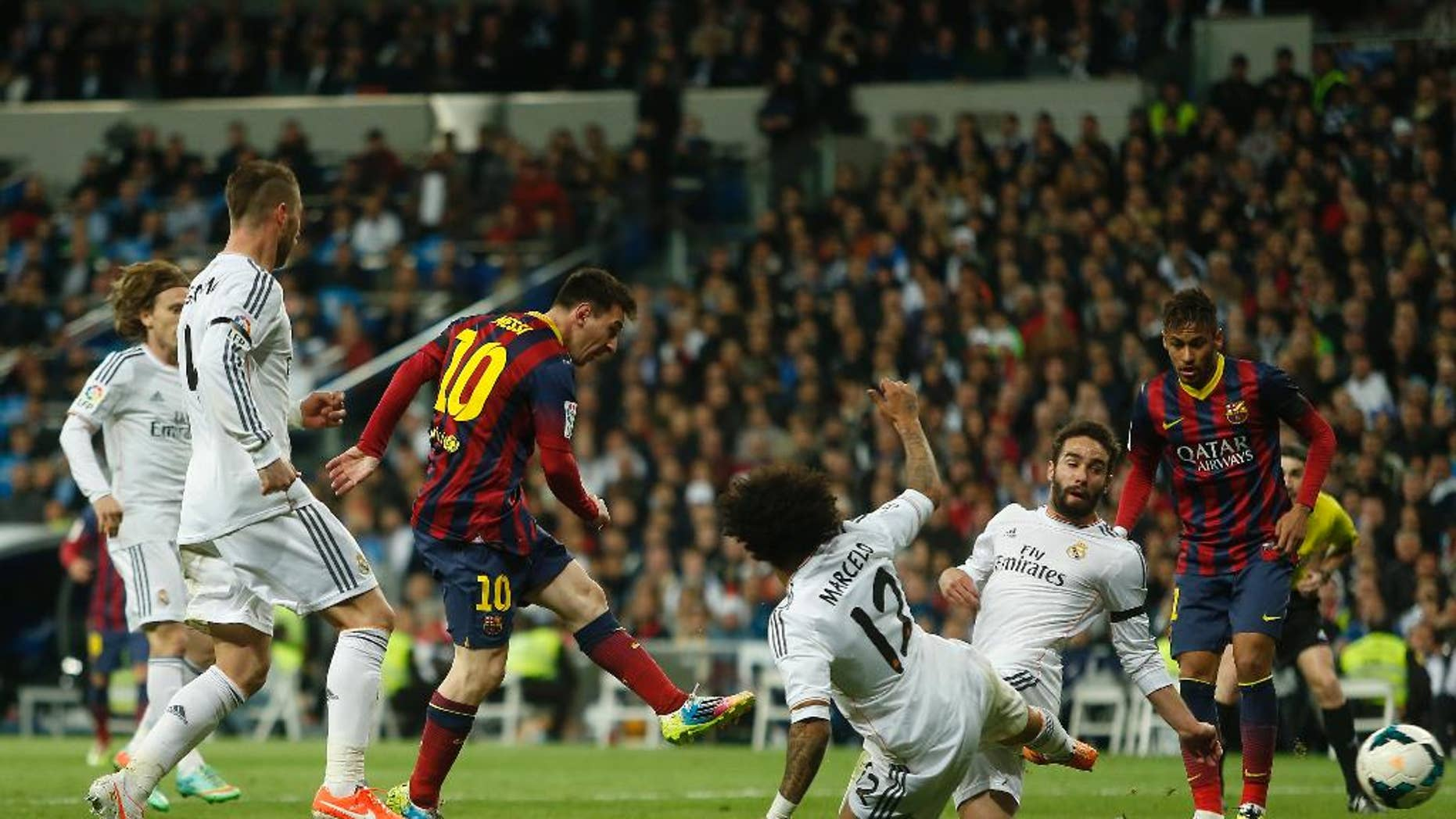 Barcelona's Lionel Messi from Argentina, centre left, scores his goal during a Spanish La Liga soccer match between Real Madrid and FC Barcelona at the Santiago Bernabeu  stadium in Madrid, Spain, Sunday, March 23, 2014. (AP Photo/Andres Kudacki)