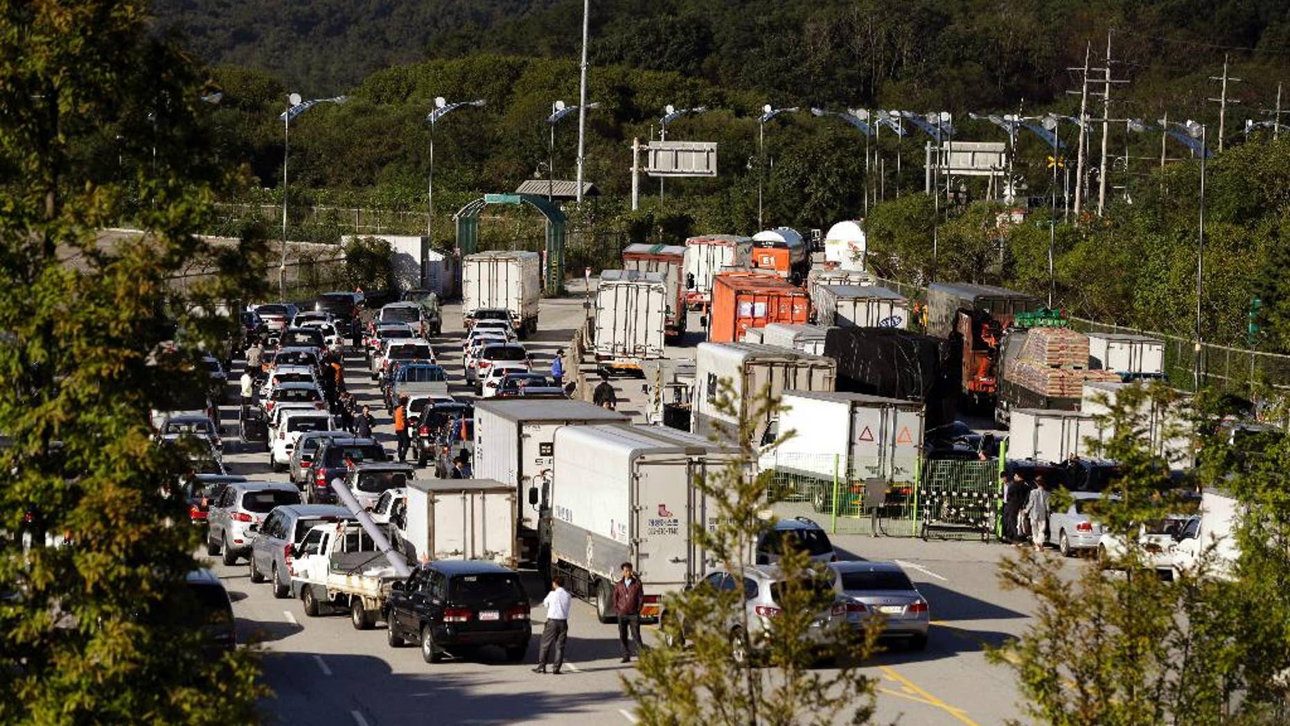 FILE - In this Sept. 16, 2013 file photo, South Korean vehicles leave for the Kaesong Industrial Complex at the customs, immigration and quarantine area of the Inter-Korean Transit Office near the border village of Panmunjom, which has separated the two Koreas since the Korean War, in Paju, north of Seoul, South Korea. North Korea on Friday, Nov. 6, 2015 lifted entry bans it had imposed earlier this week on two South Korean officials involved in managing the jointly-run factory park in the North. (AP Photo/Lee Jin-man, File)