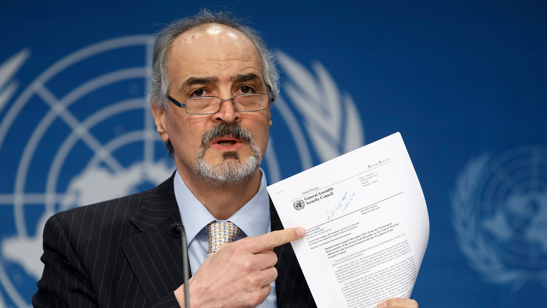 """Syrian Ambassador to the United Nations, Bashar Ja'afari, points to a document during a press conference during the Syrian peace talks in Montreux, Switzerland, Wednesday, Jan. 22, 2014. U.N. Secretary-General Ban Ki-moon opened the meeting saying that the peace talks will face """"formidable"""" challenges for Syria. Ban called on the Syrian government and the opposition trying to overthrow it to negotiate in good faith.(AP Photo/KEYSTONE/Salvatore Di Nolfi)"""