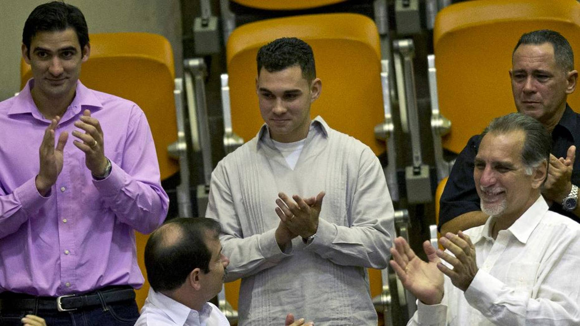 "FILE - In this Dec. 20, 2014 file photo, Elian Gonzalez, center, the young Cuban rafter who was at the center of a bitter custody battle in 2000 between relatives in Miami and his father in Cuba, is recognized with applause during the legislative session at the National Assembly in Havana, Cuba. Cuban government website Cubadebate reported Friday, July 15, 2016, the now 22-year-old Gonzalez received his diploma in industrial engineering from the University of Matanzas. Flanked by Fernando Gonzalez, bottom left, and Rene Gonzalez, front right, members of the ""Cuban Five"" spy ring. (AP Photo/Ramon Espinosa)"