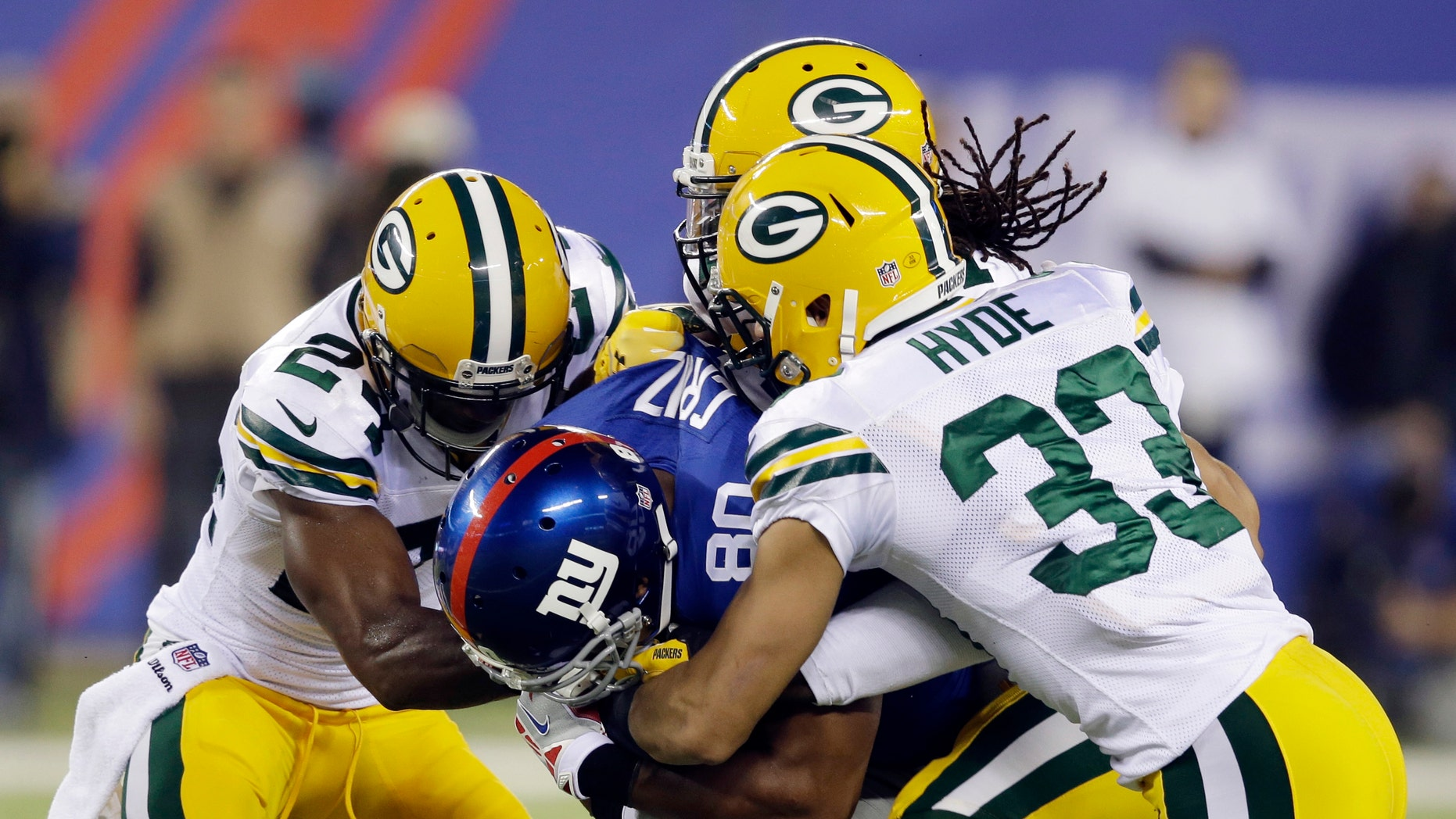 New York Giants wide receiver Victor Cruz (80) is tackled by Micah Hyde (33), Davon House, and Jarrett Bush, left, during the first half of an NFL football game Sunday, Nov. 17, 2013, in East Rutherford, N.J.  (AP Photo/Seth Wenig)