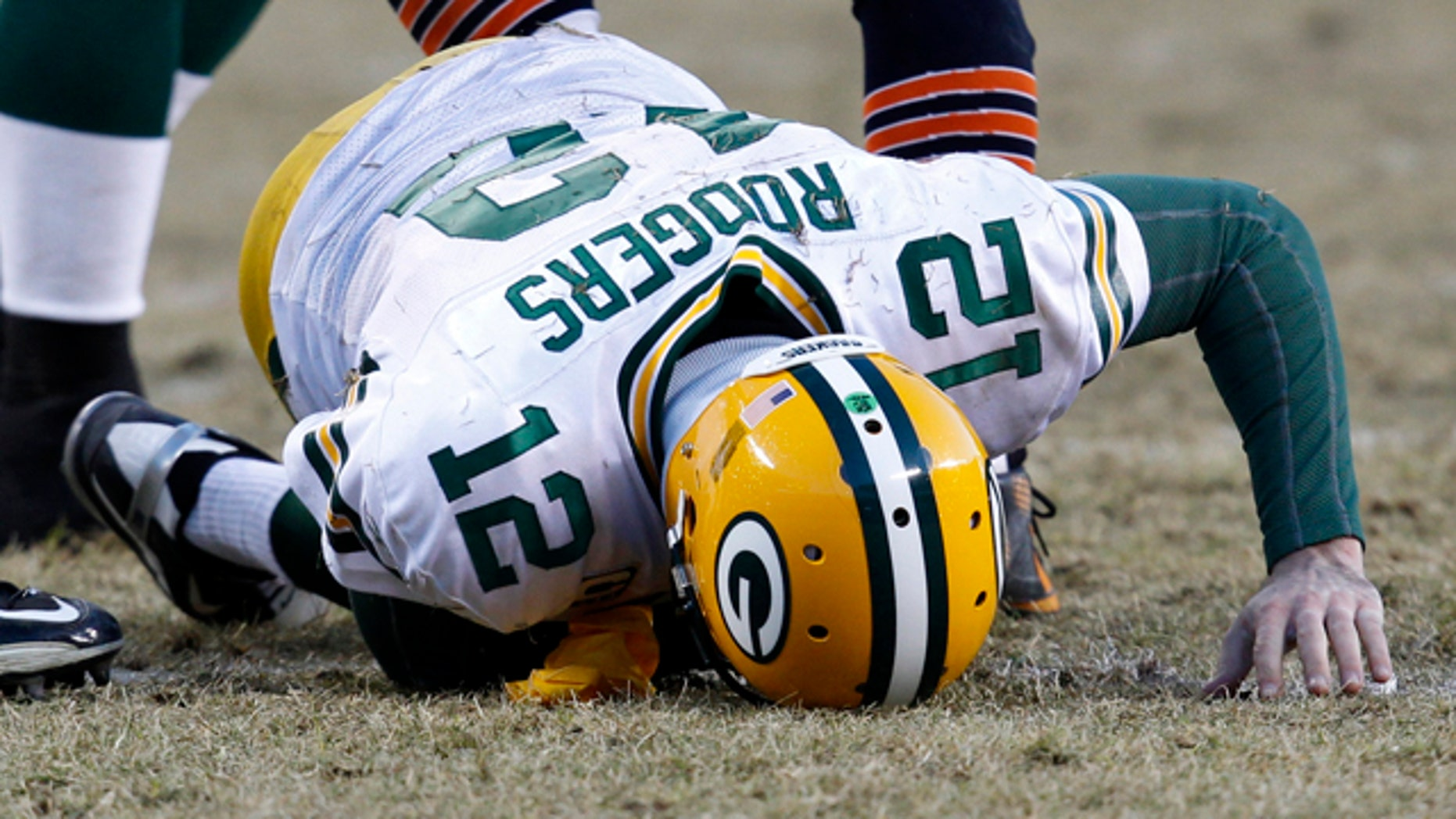 Green Bay Packers quarterback Aaron Rodgers reacts after being hit by Chicago Bears defensive end Julius Peppers during the fourth quarter of the NFC Championship football game in Chicago, January 23, 2011.
