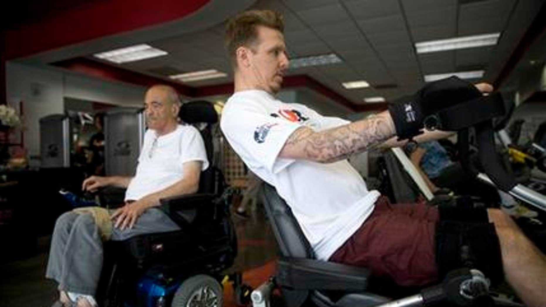 May 5, 2015: In this photo, Aaron Baker, right, a former motocross racer who was paralyzed from the neck down in a crash while practicing on a motocross track in 1999, exercises at the Center of Restorative Exercise in the Northridge section of Los Angeles.