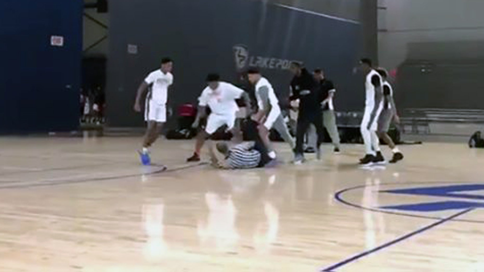 Players surrounded a fallen referee after a fight breaks out at an AAU game in Cartersville, Ga. Sunday