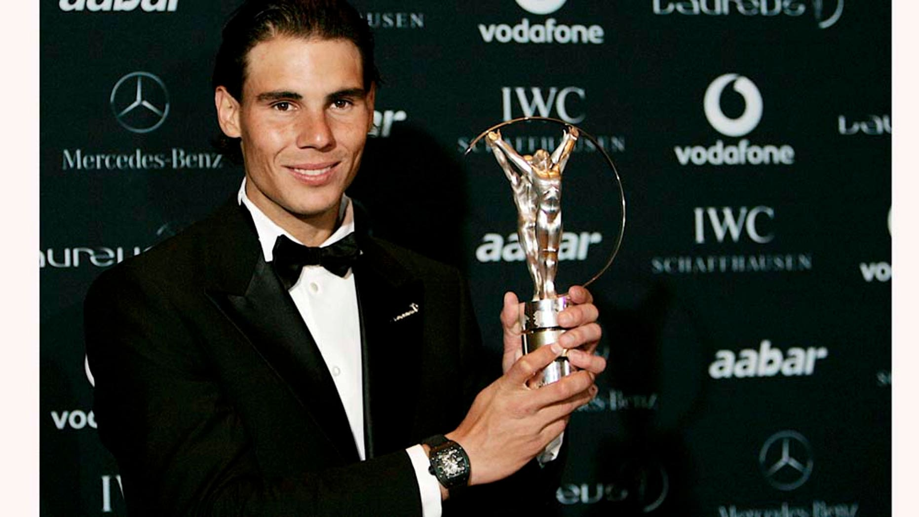 Rafael Nadal holds the trophy after winning the Laureus World Sportsman of the Year at the Laureus Awards in Abu Dhabi, United Arab Emirates, Monday Feb. 7, 2011. (AP Photo/Nousha Salimi)