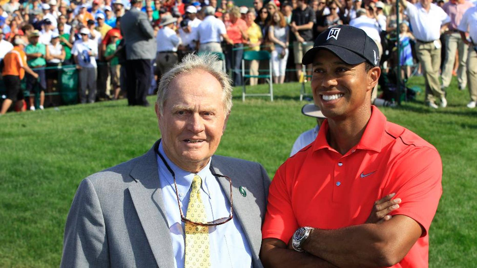 """File-This June 3, 2012, file photo shows Jack Nicklaus, left, and Tiger Woods talking after Woods won the Memorial golf tournament at the Muirfield Village Golf Club in Dublin, Ohio.  Nicklaus says he was """"painting a picture"""" when he suggested after a practice round with Tiger Woods at the 1996 Masters that Woods had the game to win at least 10 green jackets. He referred to Woods as a """"puzzle"""" on Sunday, Feb. 26, 2017, at the Honda Classic. (AP Photo/Tony Dejak, File)"""