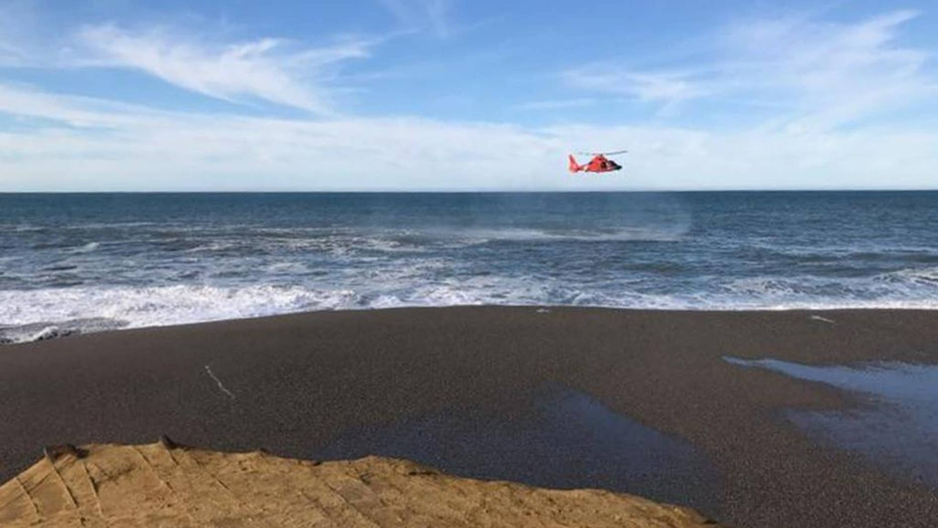 A U.S. Coast Guard helicopter searches a beach about two miles north of Cape Blanco, Oregon