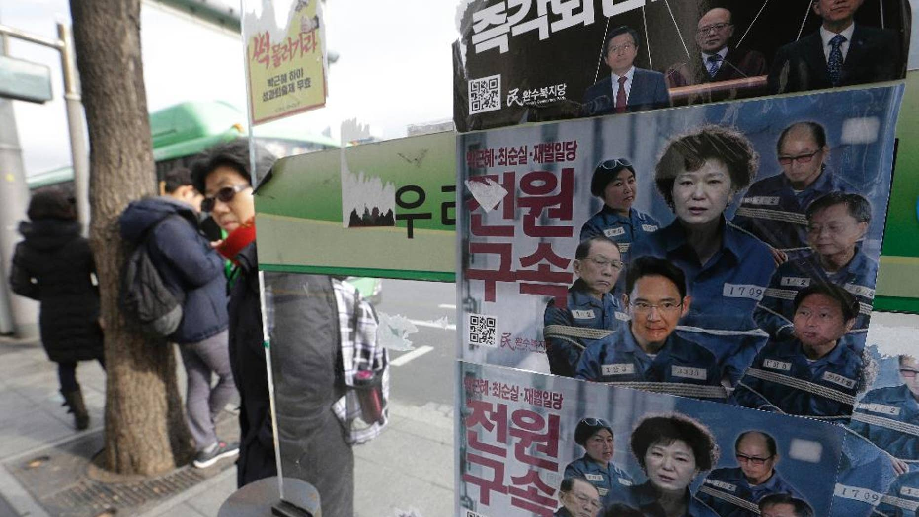"""FILE-In this Dec. 19, 2016, file photo, posters showing portraits of impeached South Korea's President Park Geun-hye, center, her aides and business men are displayed at a bus station in Seoul, South Korea. Prosecutors will not be allowed to search South Korea's presidential compound as part of their investigation of the massive corruption scandal that toppled Park from power, the president's office said Thursday, Feb. 2, 2017. The letter read """"Arrest."""" (AP Photo/Ahn Young-joon, File)"""