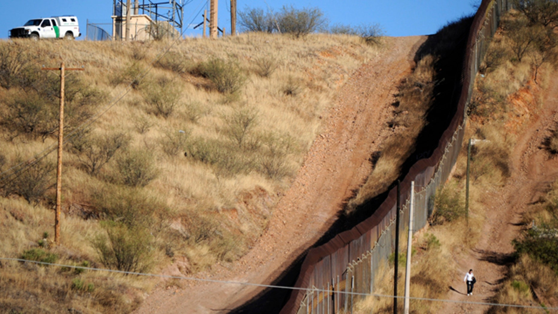 FILE 2011: A woman walks near the border fence between Mexico and the United States in Nogales.
