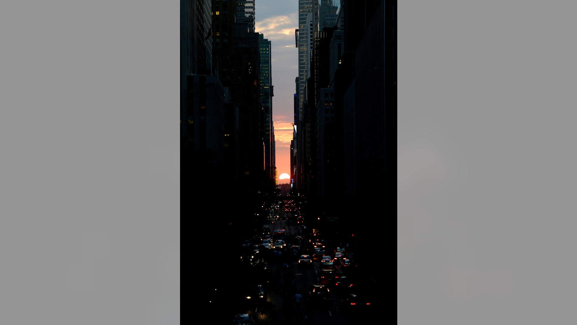 The sun sets through the middle of buildings on 42nd Street in New York's Manhattan borough, during a phenomenon known as Manhattanhenge, Wednesday, July 11, 2012. Manhattanhenge, sometimes referred to as the Manhattan Solstice, happens when the setting sun aligns with the east-to-west streets of the main street grid. The term references Stonehenge, at which the sun aligns with the stones on the solstices in England. (AP Photo/Julio Cortez)
