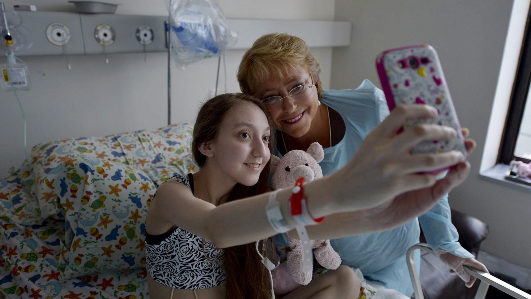 """In this photo released by Chile's presidential press office, President Michelle Bachelet, right, poses for a selfie with Valentina Maureira, who suffers from cystic fibrosis, at a hospital in Santiago, Chile, Saturday, Feb. 28, 2015. Maureira posted a video on the web asking a meeting with Bachelet to allow her to """"sleep for ever"""". (AP Photo/Chile's presidential press office"""