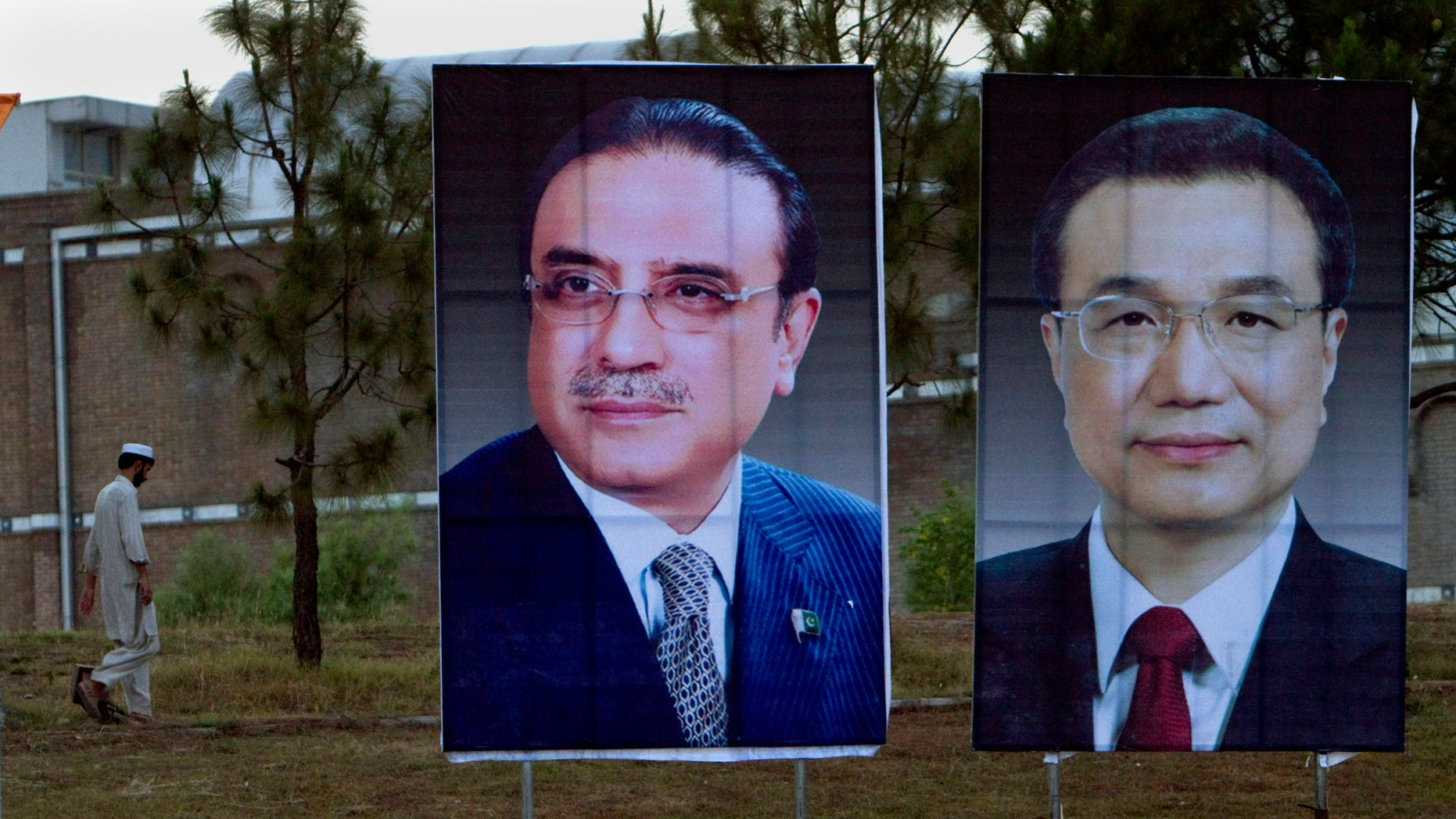 A man walks next to huge portraits of Chinese Premier Li Keqiang, right, and Pakistani President Asif Ali Zardari, left, displayed near the presidency in Islamabad, Pakistan. Keqiang will arrive in Islamabad on May 22 on a two day official visit to hold talks with Pakistani leadership to discuss international, regional issues and enhance co-operation in bilateral ties. (AP Photo/Anjum Naveed)