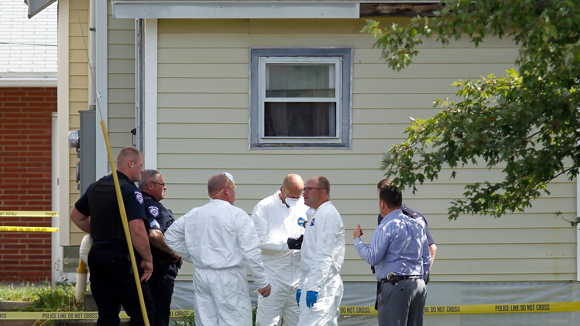 Authorities execute a search warrant on a home on Tuesday in Ashland, Ohio.