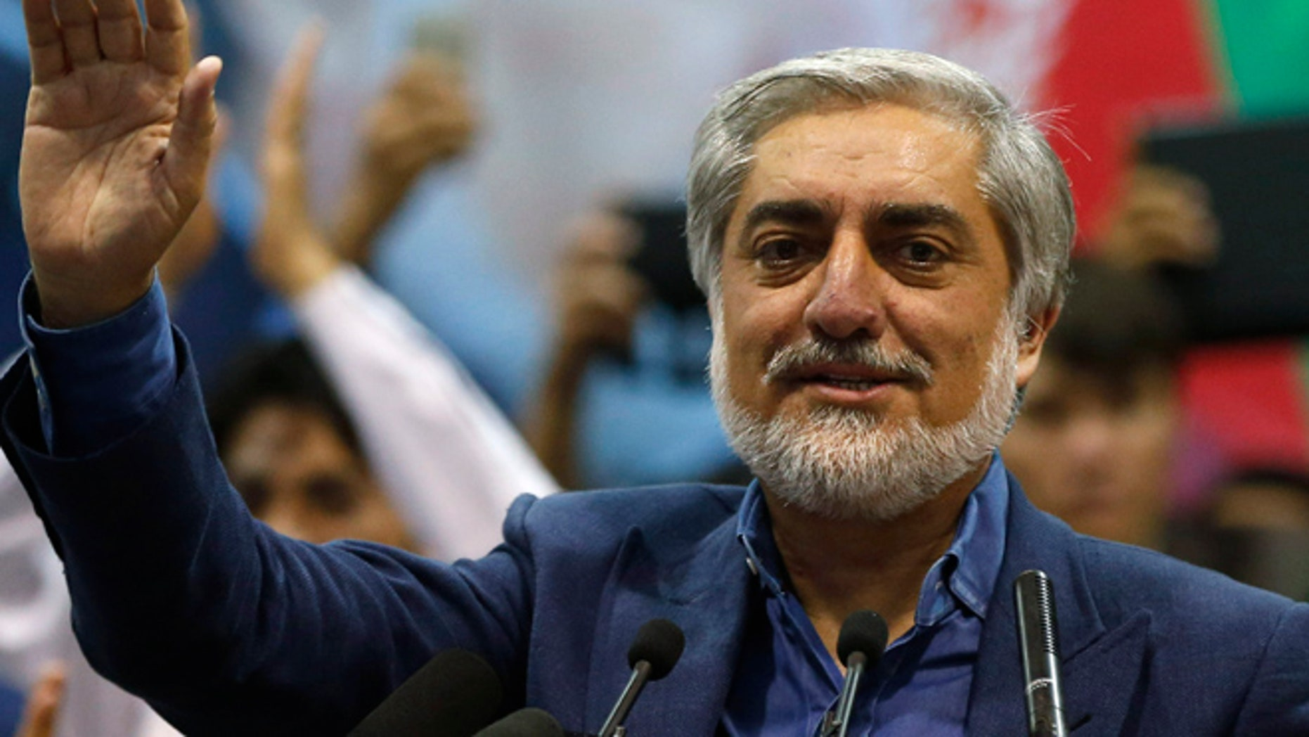 July 8: Afghan presidential candidate Abdullah Abdullah waves to his supporters during a gathering in Kabul. Abdullah told thousands of supporters on Tuesday he was the winner of last month's run-off election.