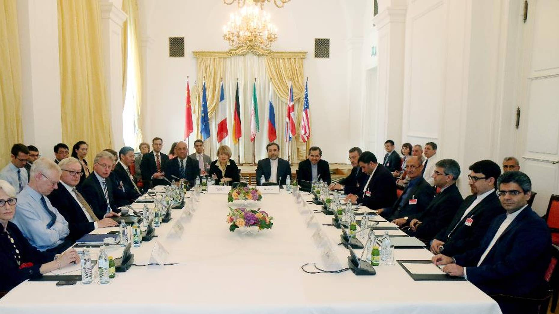FILE - In this Friday, June 12, 2015 file photo delegates sit around a table prior to a bilateral meeting as part of the closed-door nuclear talks with Iran at a hotel in Vienna, Austria. Iran and six powers are still apart on all main elements of a nuclear deal with less than two weeks to go to their June 30 target date and will likely have to extend their negotiations, two diplomats tell The Associated Press. (AP Photo/Ronald Zak, File)