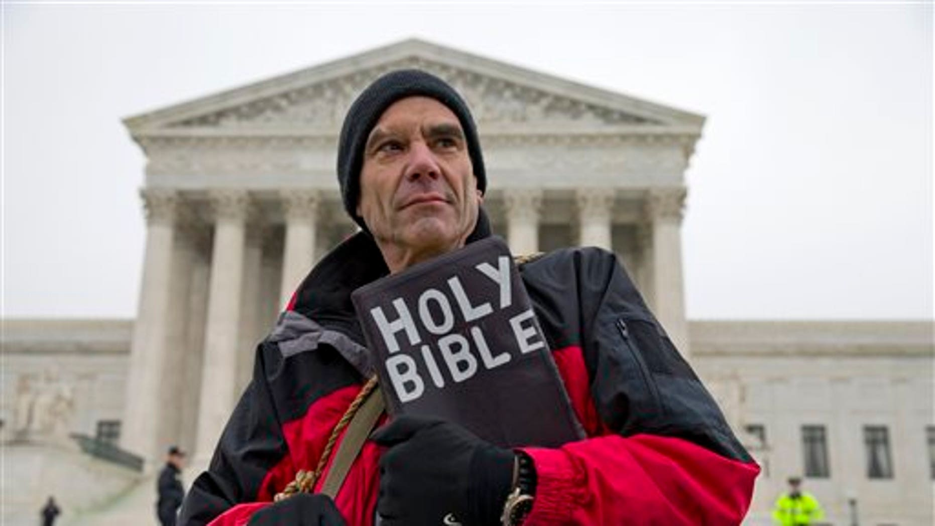 In this Jan. 15, 2014 file photo, Alan Hoyle, of Lincolnton, N.C., stands outside the Supreme Court in Washington, Wednesday, Jan. 15, 2014, where the court heard arguments on a state of Massachusetts law setting a 35-foot (10 meter) protest-free zone outside abortion clinics. (AP Photo/ Evan Vucci, File)