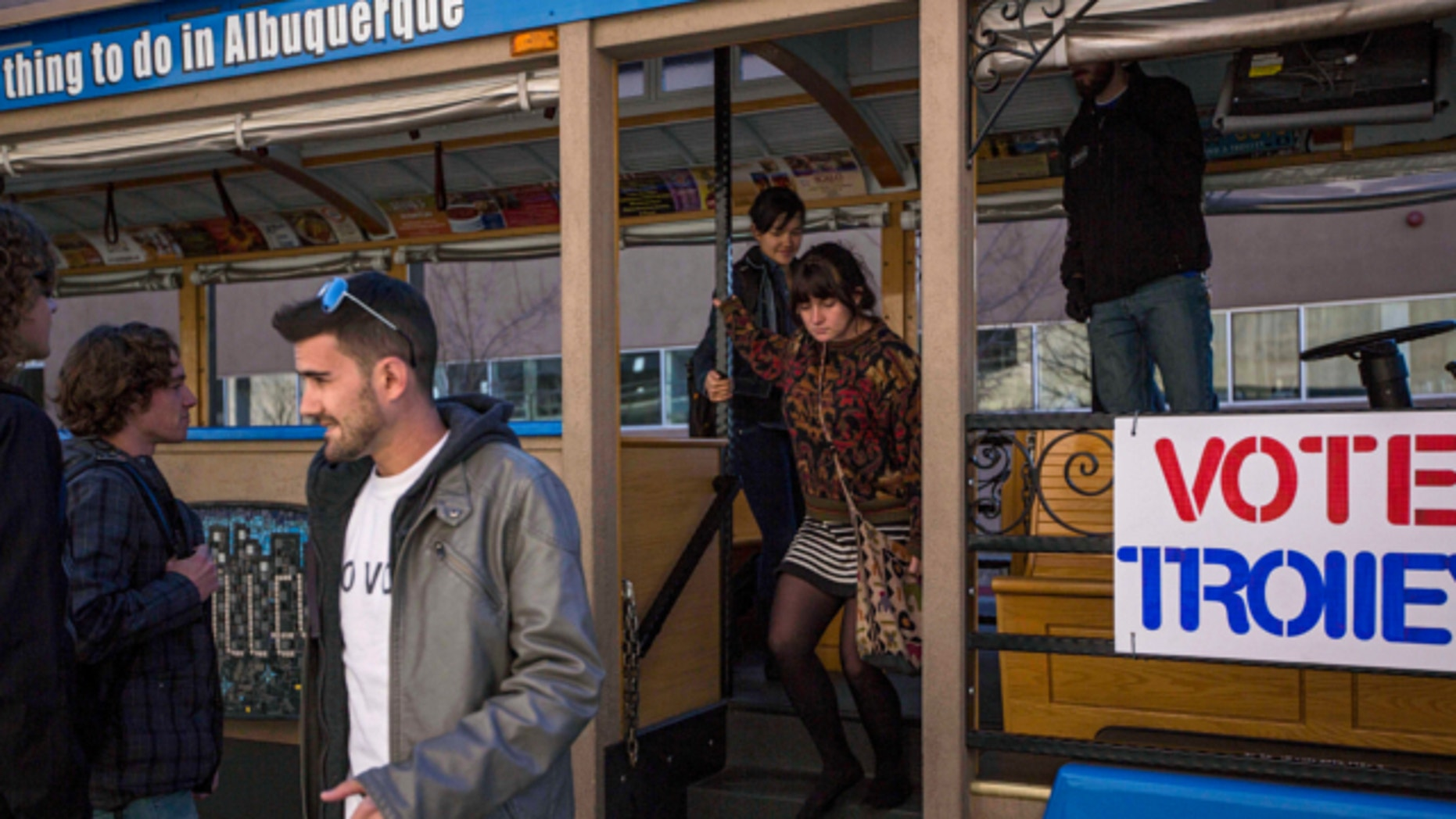 """Nov. 14, 2013: University of New Mexico students exit the """"Voting Trolly"""" at a stop on campus in Albuquerque, N.M."""