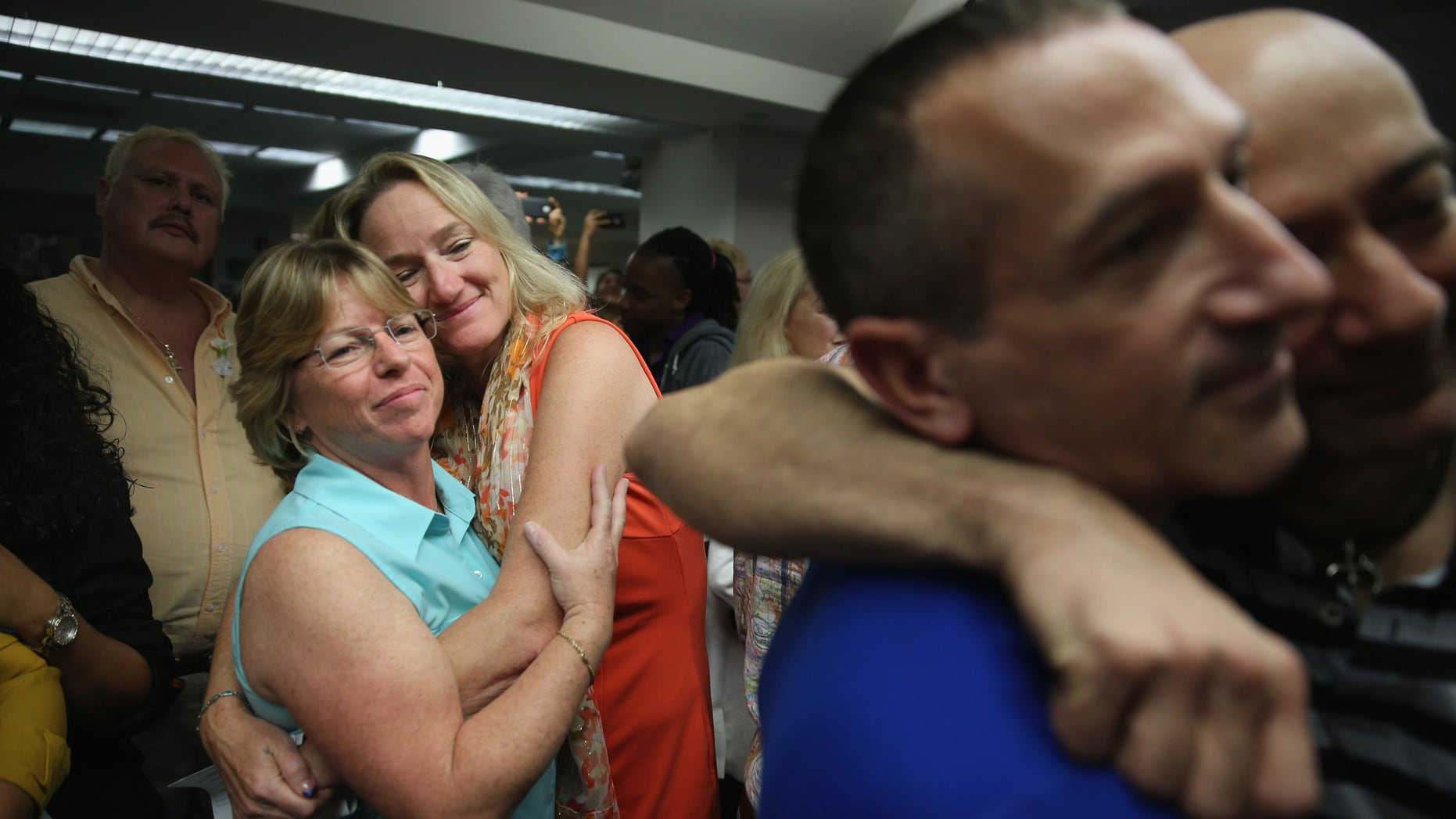 FORT LAUDERDALE, FL - JANUARY 06:  Couples embrace as they attend a wedding ceremony at the Broward County Courthouse on January 6, 2015 in Fort Lauderdale, Florida. Gay marriage is now legal statewide after the courts ruled that the ban on gay marriage is unconstitutional and the Supreme Court declined to intervene.  (Photo by Joe Raedle/Getty Images)