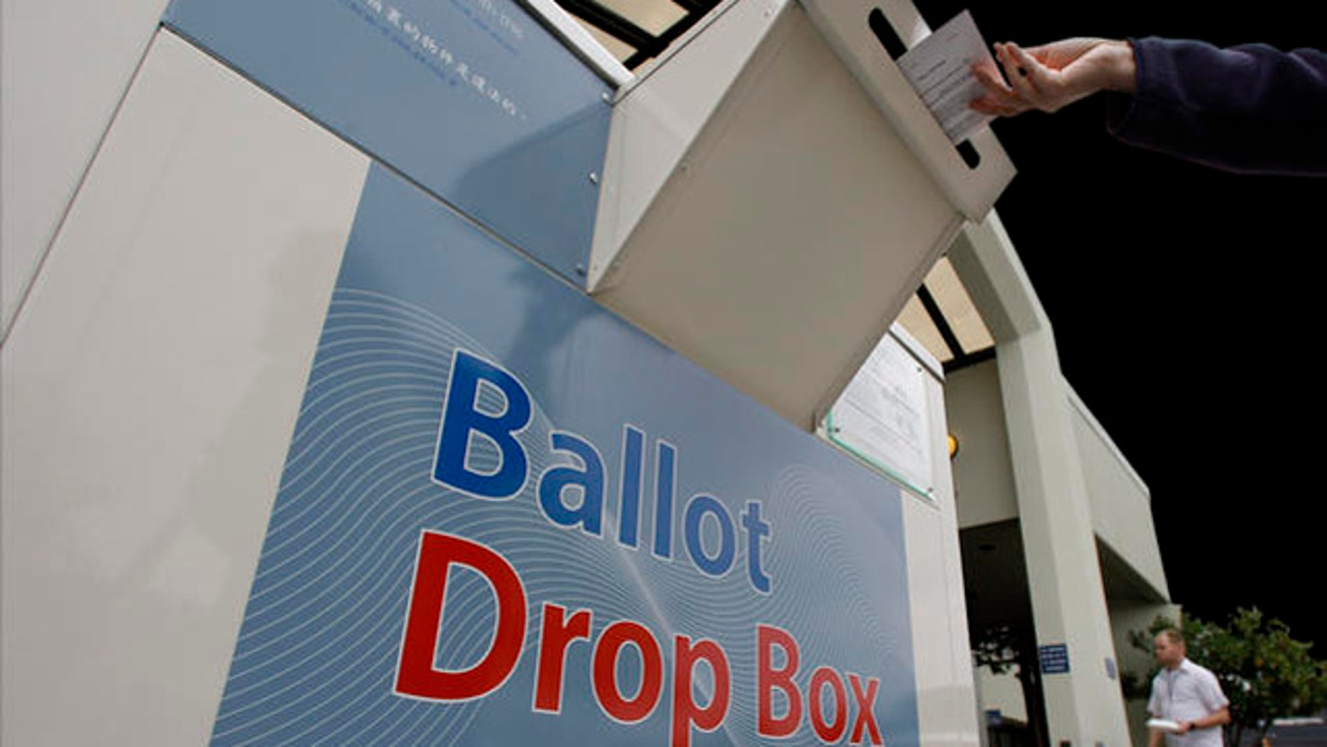 A voter drops an absentee ballot into a collection box Thursday, Oct. 30, 2008, at the King County Elections office in Renton, Wash. In-person accessible voting, on units providing audio and touch-screen ballots in English and Chinese, is available for all King County voters at the site through Saturday, Nov. 1, and on Monday, Nov. 3. (AP Photo/Elaine Thompson)