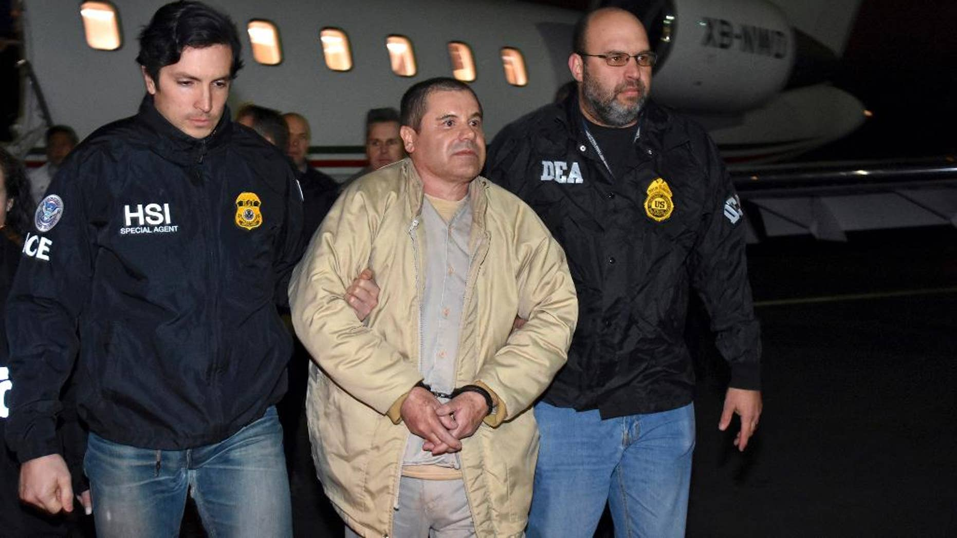 "FILE - In this Jan. 19, 2017 file photo provided by U.S. law enforcement, authorities escort Joaquin ""El Chapo"" Guzman, center, from a plane to a waiting caravan of SUVs at Long Island MacArthur Airport, in Ronkonkoma, N.Y. U.S. District Judge Brian Cogan ruled Thursday, May 4, 2017, that Guzman needs to stay in solitary confinement at a New York City lockup to keep him from trying to control his drug-trafficking empire from behind bars. Cogan rejected a request by Guzman's defense team to order him released from an ultrahigh-security wing of a jail in lower Manhattan and be allowed in the general inmate population and receive visitors. (U.S. law enforcement via AP, File)"