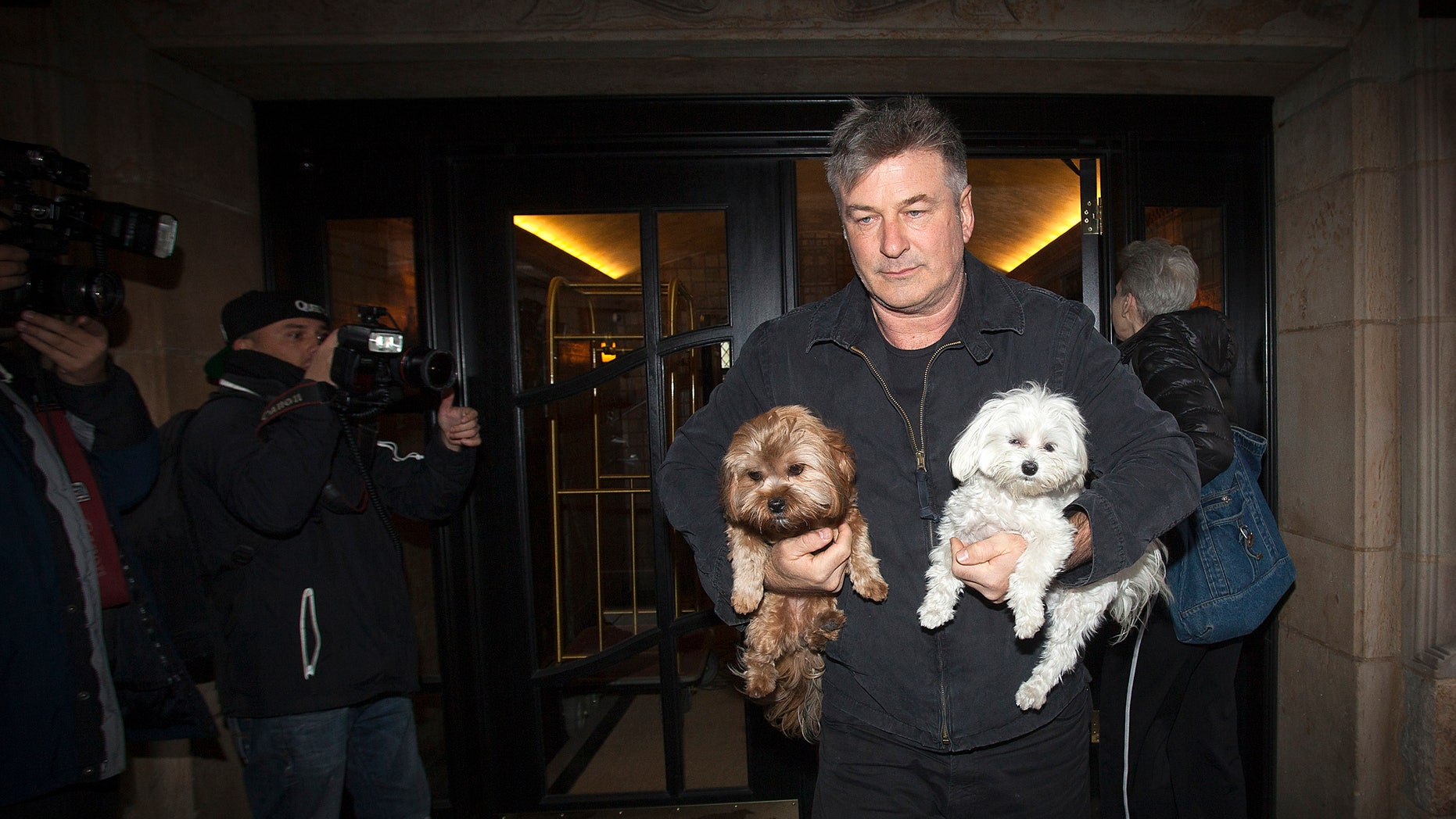 November 15, 2013.Actor Alec Baldwin walks out of his apartment building carrying two dogs in New York. Baldwin assaulted a reporter earlier in the day, according to local media. In the earlier incident, he smacked a mobile phone from the reporter's hands and shoved him against a car.