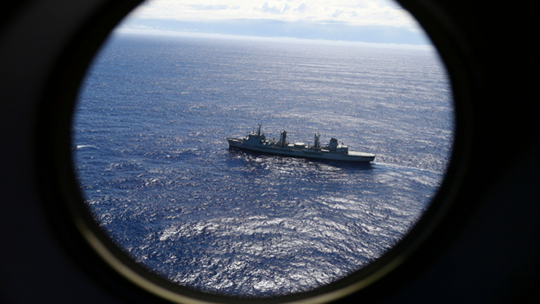 FILE - In this March 31, 2014 file photo, HMAS Success scans the southern Indian Ocean, near the coast of Western Australia, as a Royal New Zealand Air Force P3 Orion flies over, while searching for missing Malaysia Airlines Flight MH370.