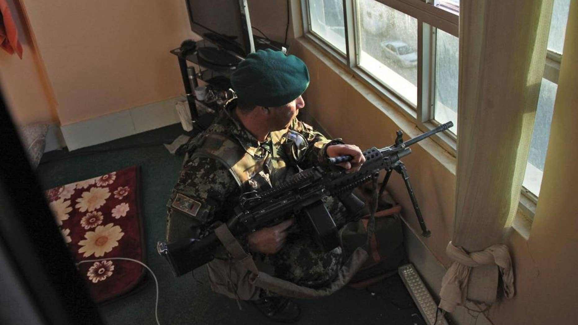 An Afghanistan's National Army (ANA) soldier takes up position near the site of a clash between insurgents and security forces at the Indian Consulate in Herat, Afghanistan, Friday, May 23, 2014. Gunmen armed with machine guns and rocket-propelled grenades attacked the Indian Consulate in western Afghanistan's Herat province Friday, an assault that injured no diplomatic staff, police said. Indian officials said there had been a threat against its diplomats in Afghanistan, but gave no other details. (AP Photo/Hoshang Hashimi)
