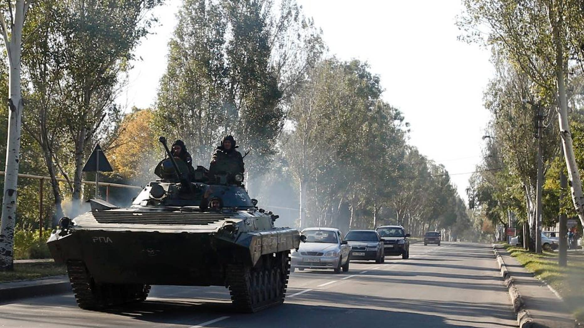 A pro-Russian  armored personal carrier passes through the town of Donetsk, eastern Ukraine, Thursday, Oct. 2, 2014. Pro-Russian rebels in eastern Ukraine advanced Wednesday on the government-held airport in Donetsk, pressing to seize the key transportation hub even as the two sides bargained over a troop pullout under a much-violated truce. (AP Photo/Darko Vojinovic)
