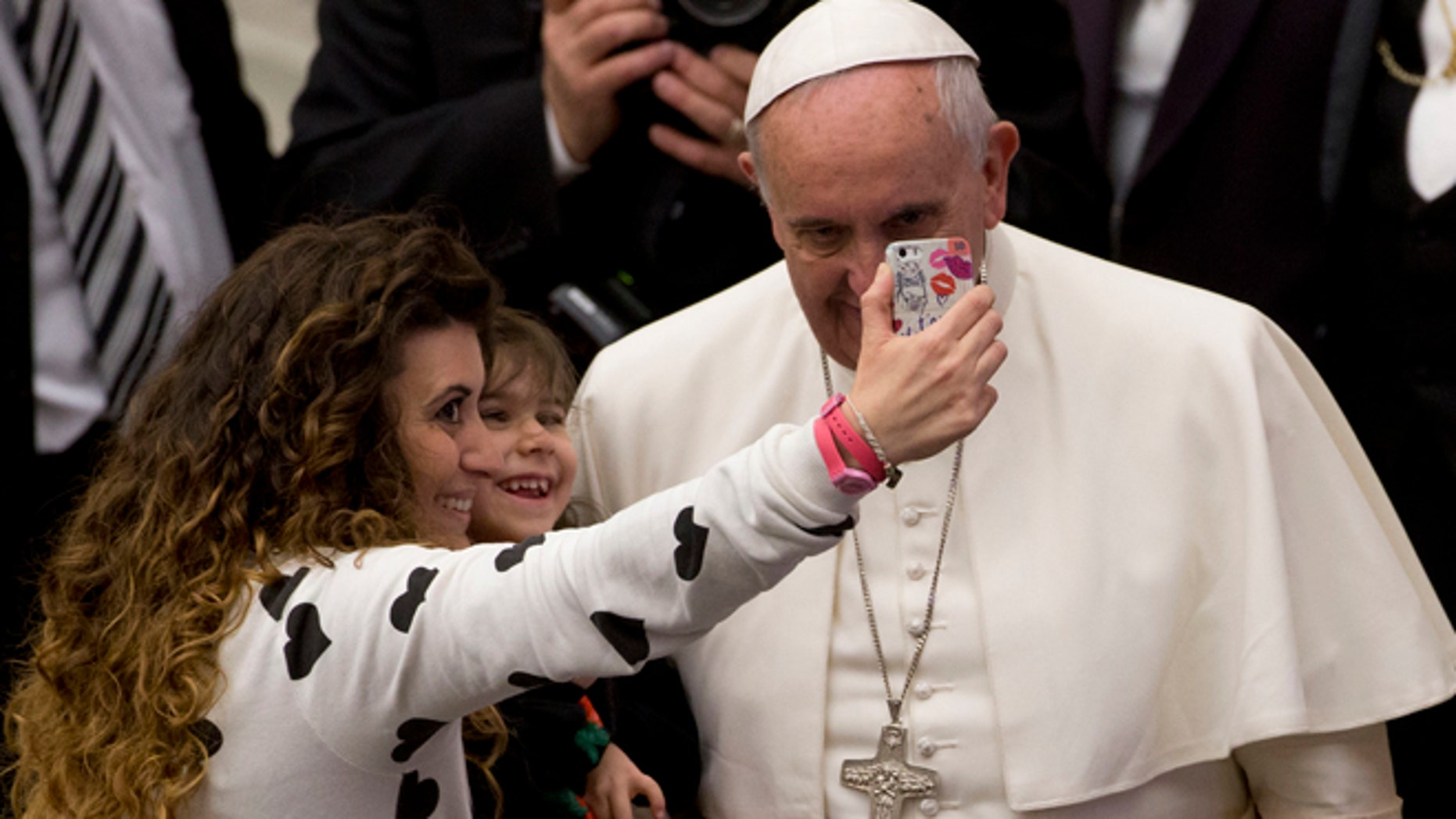 """A woman and a child take a selfie photo with Pope Francis, right, during his weekly general audience in the Paul VI hall at the Vatican, Wednesday, Jan. 21, 2015. Pope Francis is praising big families after saying Catholics don't have to breed """"like rabbits."""" He says big families are a gift and don't cause poverty in the developing world, and that the real cause of poverty is an unjust economic system that idolizes money over people. (AP Photo/Andrew Medichini)"""